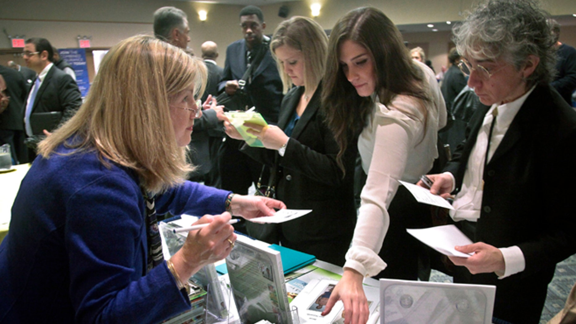 Oct. 24, 2012: Patricia Mazza, left, meets job seekers, including recent college grads Ashley Deyo, 22, second from left, and Chyna Dama, 23, second from right, during a National Career Fairs' job fair in New York.