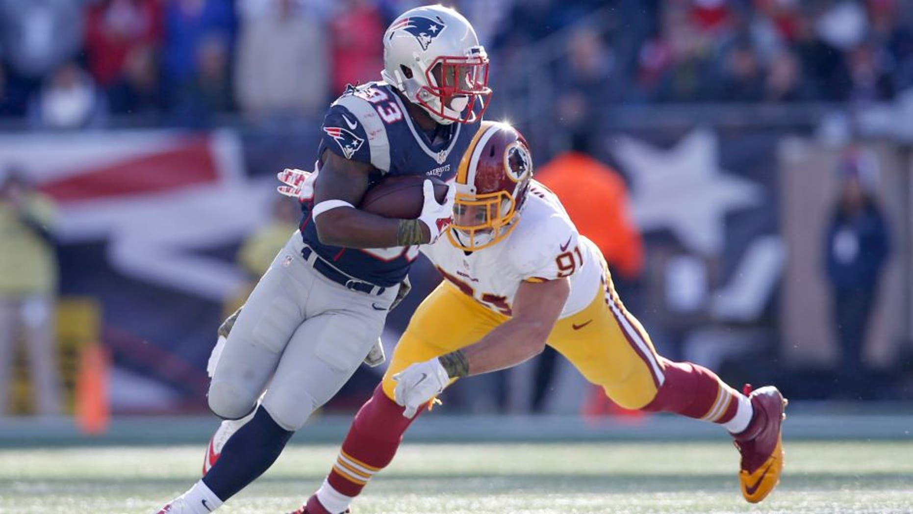 Nov 8, 2015; Foxborough, MA, USA; New England Patriots running back Dion Lewis (33) is tackled by Washington Redskins outside linebacker Ryan Kerrigan (91) during the first quarter at Gillette Stadium. Mandatory Credit: Greg M. Cooper-USA TODAY Sports