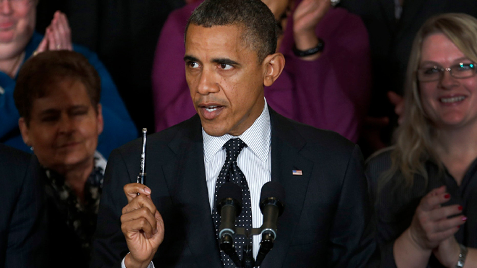 Nov. 9, 2012: President Barack Obama holds up a pen as he speaks about the economy and the deficit.