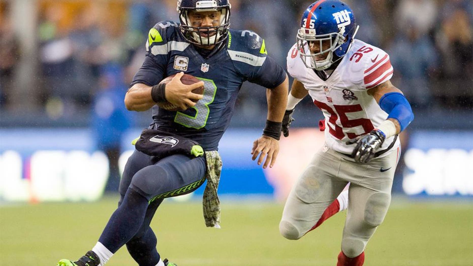 Nov 9, 2014; Seattle, WA, USA; Seattle Seahawks quarterback Russell Wilson (3) carries the ball while being chased by New York Giants free safety Quintin Demps (35) during the second half at CenturyLink Field. Seattle defeated New York 38-17. Mandatory Credit: Steven Bisig-USA TODAY Sports
