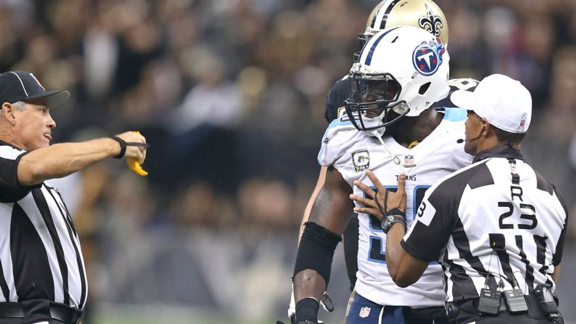 Nov 8, 2015; New Orleans, LA, USA; Tennessee Titans outside linebacker Brian Orakpo (98) is held back by referee Jerome Boger (23) while line judge Jeff Seeman throws a flag in the second half of their game against the New Orleans Saints at the Mercedes-Benz Superdome. The Titans won, 34-28, in overtime. Mandatory Credit: Chuck Cook-USA TODAY Sports