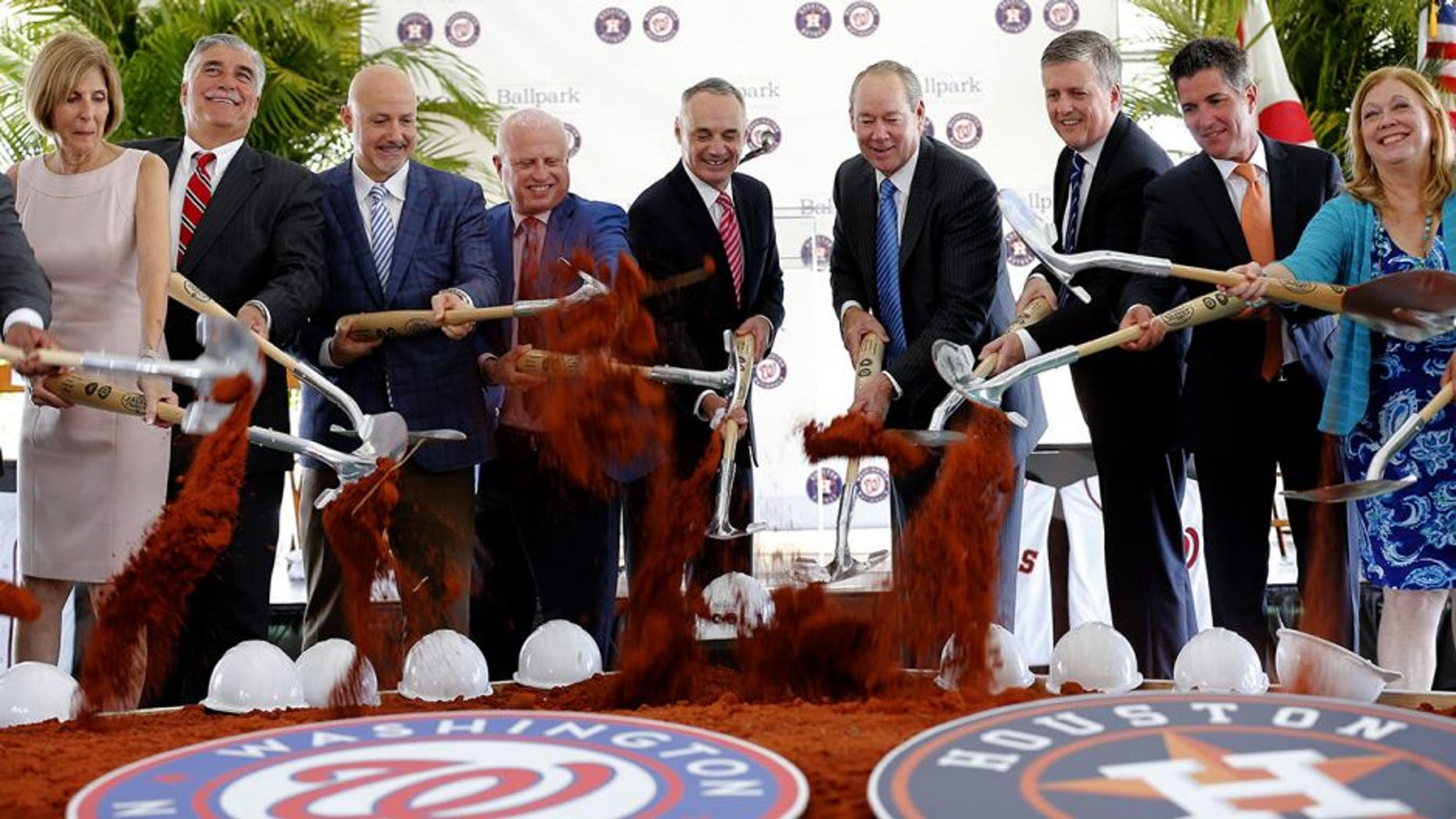 Major League Baseball commissioner Rob Manfred, center left, is flanked by Houston Astros owner Jim Crane, right center, and Washington Nationals owner Mark Lerner, left center, along with other dignitaries during a groundbreaking ceremony for the future home of the of Houston Astros and the Washington Nationals spring training facility on Monday, Nov. 9, 2015, in West Palm Beach, Fla. (AP Photo/Steve Mitchell)