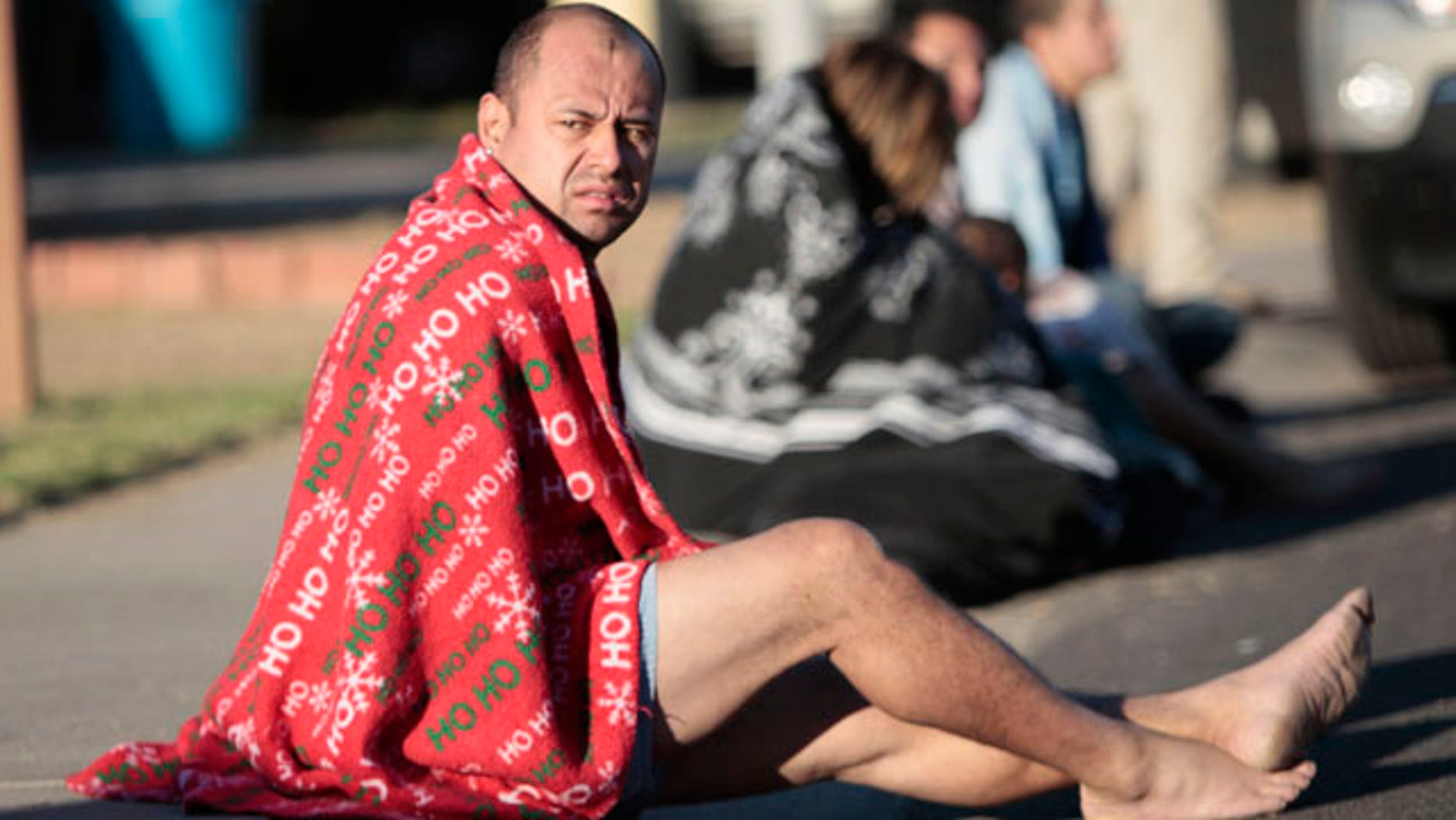 Nov. 10: Mark Rodriguez-Banks sits on the ground during a raid in Phoenix.