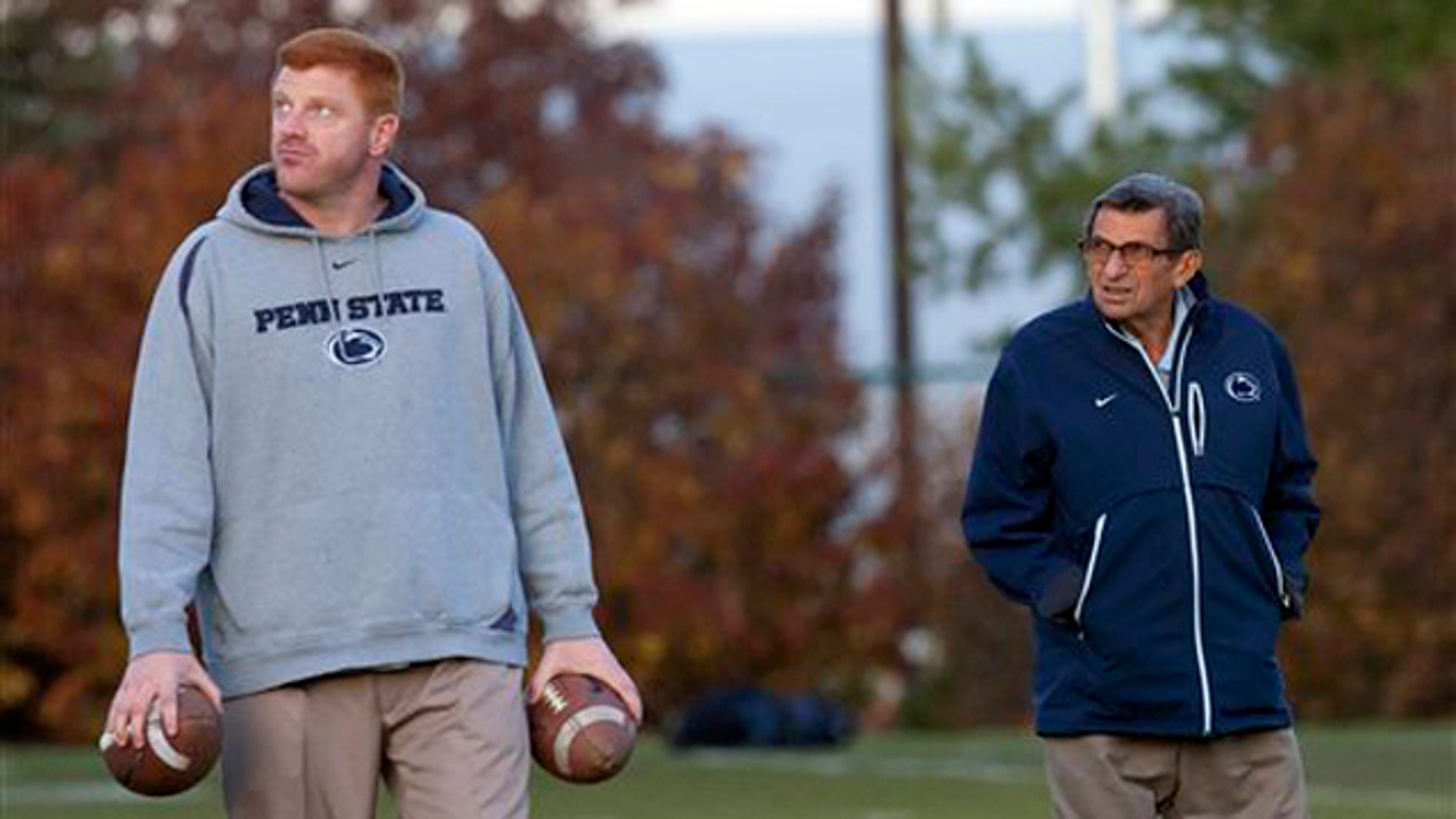 November 9, 2011: Former Penn State football coach Joe Paterno, right, and assistant coach Mike McQueary walk the field during practice.