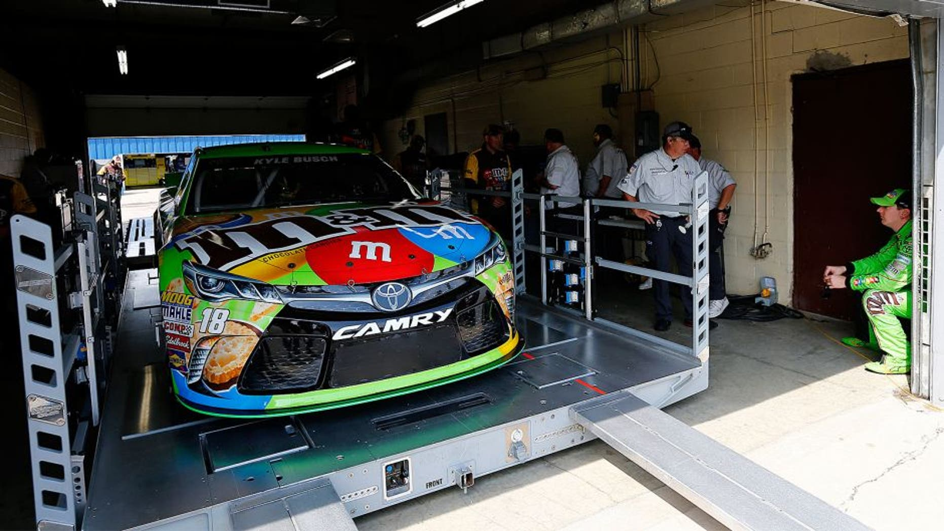 BROOKLYN, MI - JUNE 12: Kyle Busch, driver of the #18 M&M's Crispy Toyota, waits as his car goes through technical inspection prior to qualifying for the NASCAR Sprint Cup Series Quicken Loans 400 at Michigan International Speedway on June 12, 2015 in Brooklyn, Michigan. (Photo by Jonathan Ferrey/NASCAR via Getty Images)