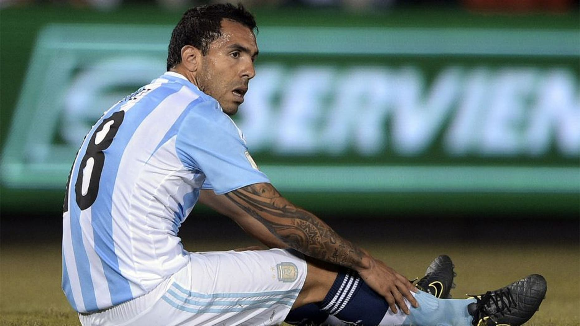 Argentina's forward Carlos Tevez sits on the ground during the Russia 2018 FIFA World Cup South American Qualifiers football match against Paraguay, at the Defensores del Chaco stadium in Asuncion, on October 13, 2015. AFP PHOTO / JUAN MABROMATA (Photo credit should read JUAN MABROMATA/AFP/Getty Images)