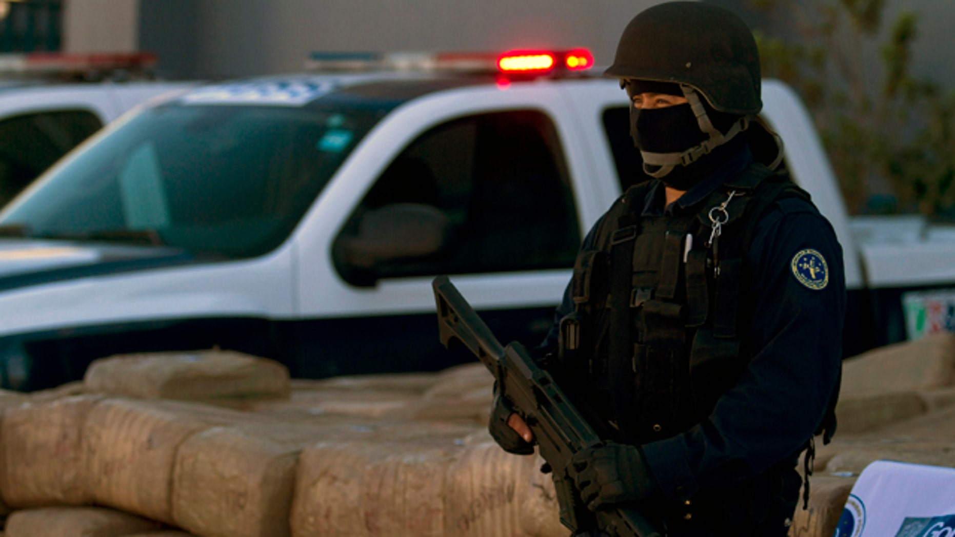 Nov. 1: A police officer stands guard by seized marijuana at the Baja California state police headquarters in Tijuana, Mexico.