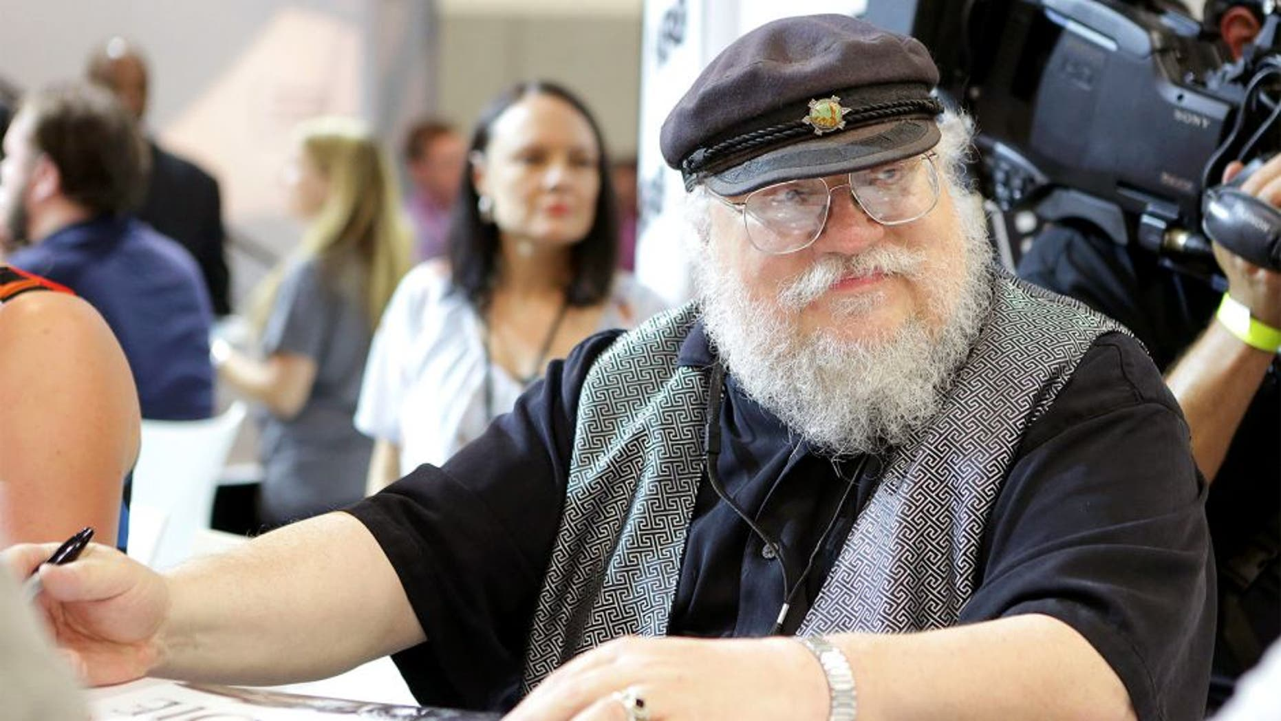 """SAN DIEGO, CA - JULY 25: Writer George R.R. Martin of """"Game of Thrones"""" signs autographs during the 2014 Comic-Con International Convention-Day 3 at the San Diego Convention Center on July 25, 2014 in San Diego, California. (Photo by Tiffany Rose/Getty Images)"""
