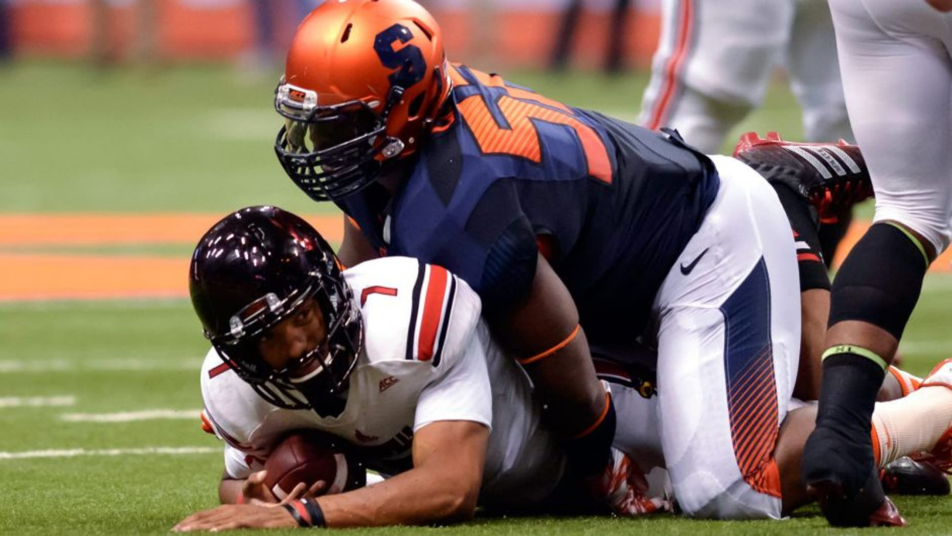 Oct 3, 2014; Syracuse, NY, USA; Louisville Cardinals quarterback Reggie Bonnafon (7) is sacked by Syracuse Orange nose tackle Eric Crume (52) during the second quarter of a game at the Carrier Dome. Mandatory Credit: Mark Konezny-USA TODAY Sports