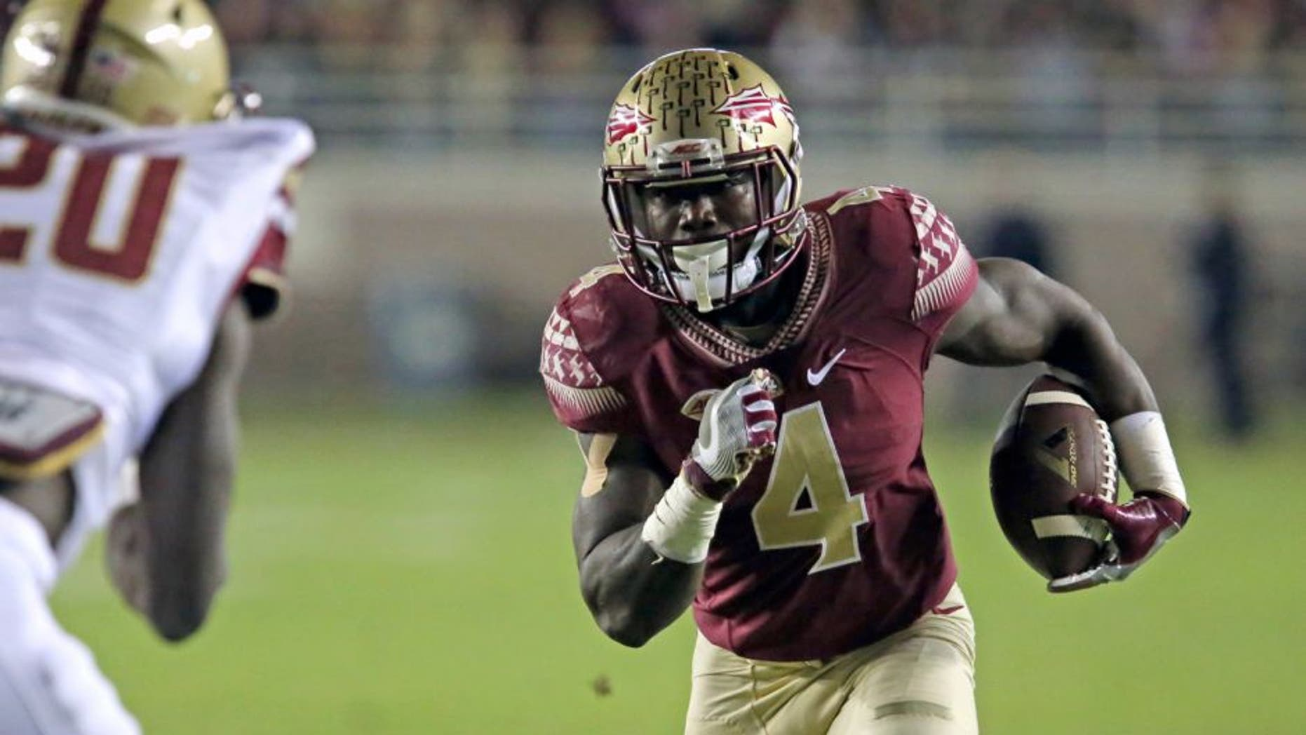 Florida State's Dalvin Cook picks up yardage as Boston College's defender Isaac Yiadom moves in for the tackle in the first half of an NCAA college football game, Friday, Nov. 11, 2016, in Tallahassee, Fla. (AP Photo/Steve Cannon)