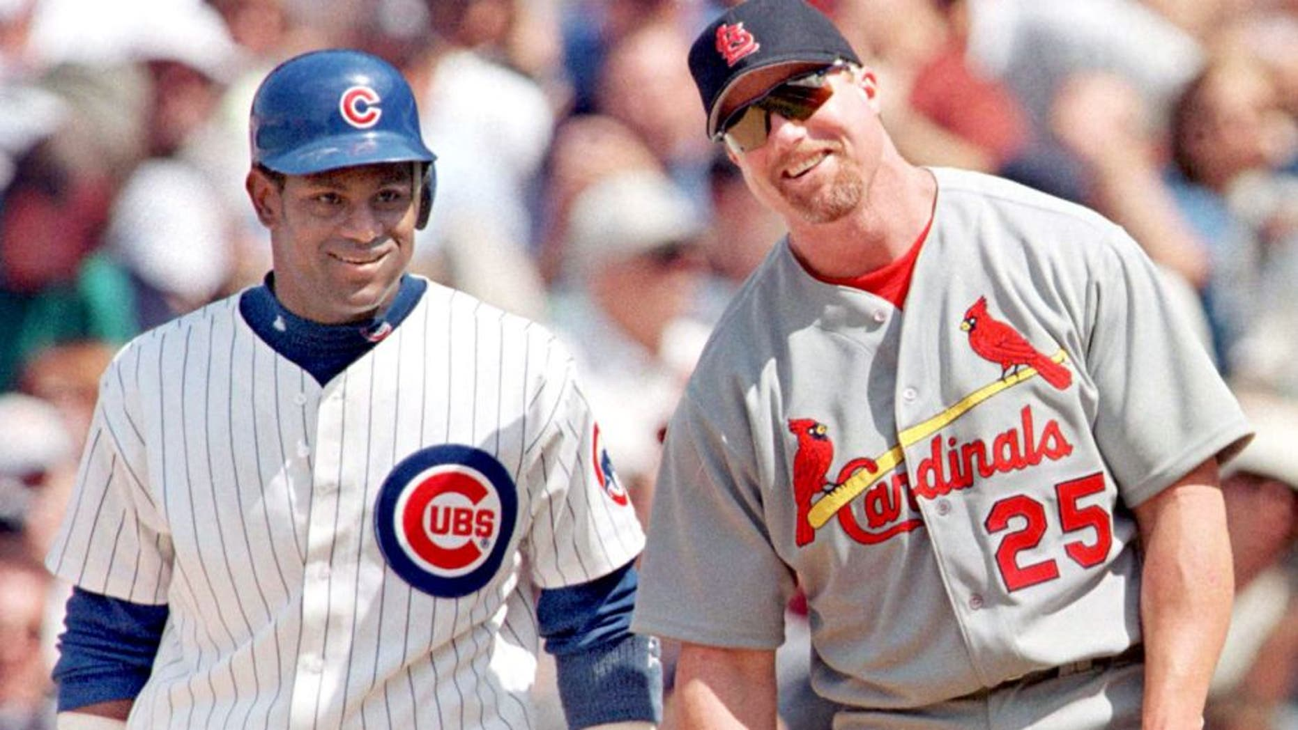 CHICAGO, UNITED STATES: The Chicago Cubs' Sammy Sosa stands with St. Louis Cardinal's first baseman Mark McGwire between pitches after Sosa singled in the second inning 28 May, 1999, at Wrigley Field in Chicago, Illinois. It was the first time the pair had played each other since last year's home run race. The Cubs won 6-3 with help from a home run from Sosa. AFP PHOTO/John ZICH (Photo credit should read JOHN ZICH/AFP/Getty Images)