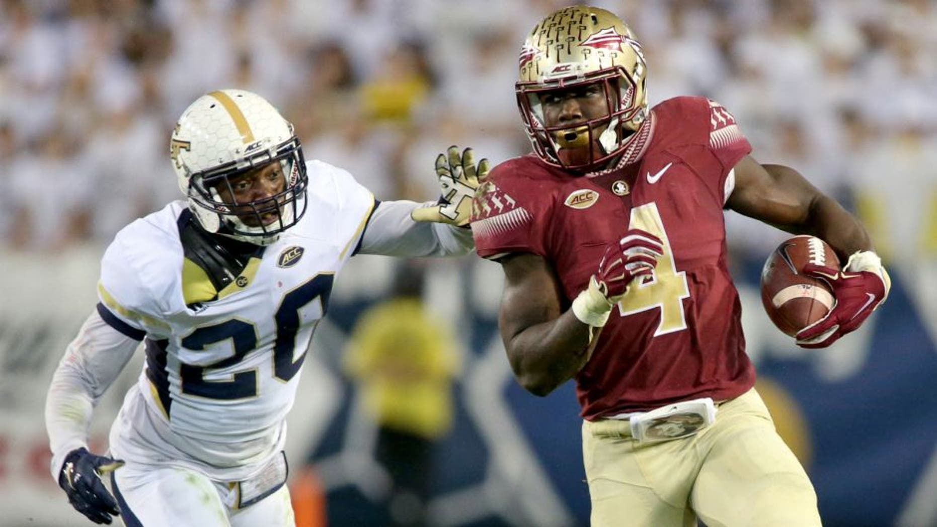 Oct 24, 2015; Atlanta, GA, USA; Florida State Seminoles running back Dalvin Cook (4) runs against Georgia Tech Yellow Jackets defensive back Lawrence Austin (20) in the second quarter of their game at Bobby Dodd Stadium. Mandatory Credit: Jason Getz-USA TODAY Sports
