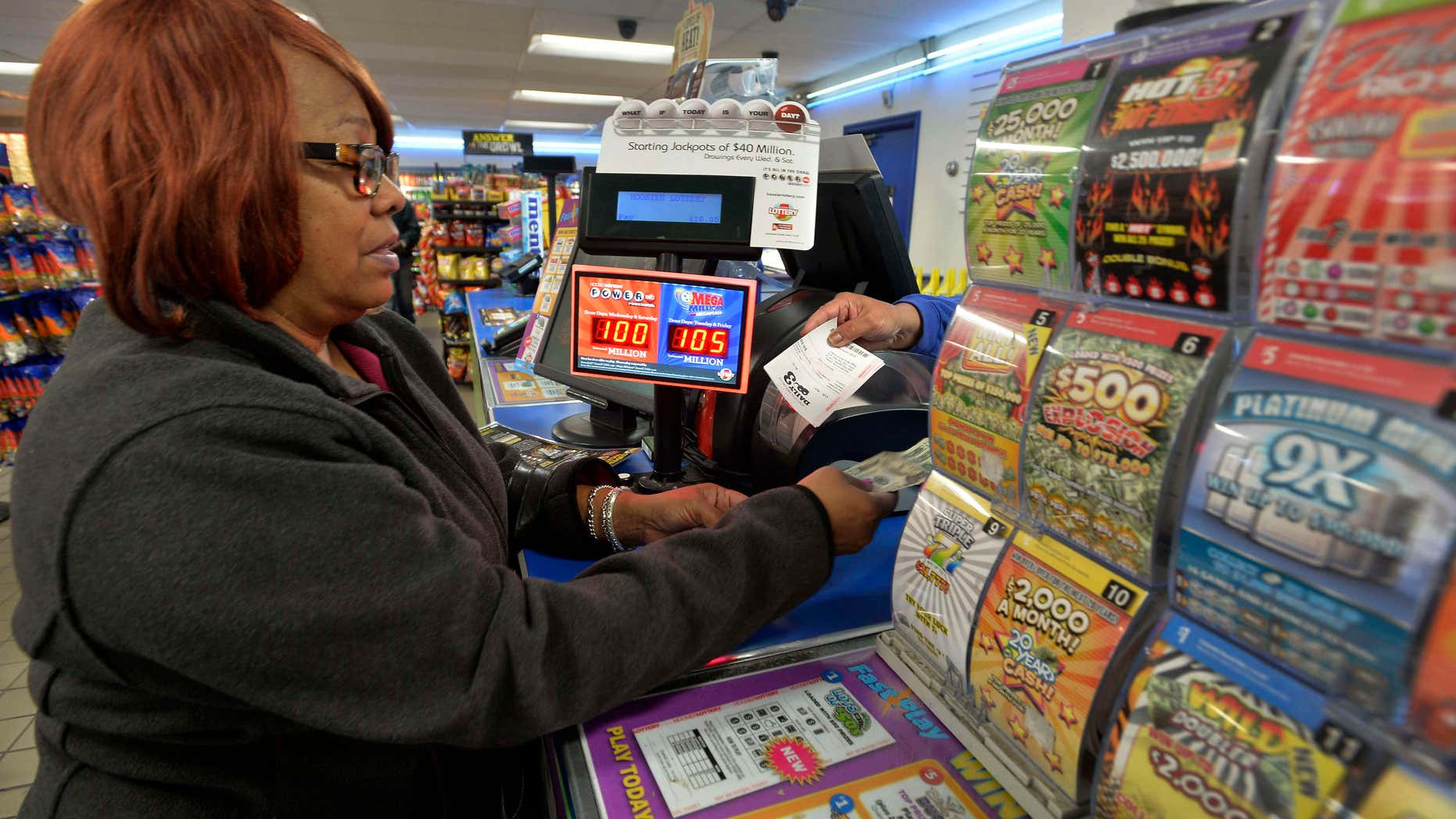 FILE - In this Oct. 23, 2015 file photo, Vera Washington of Chicago, buys lotto tickets at the K&D Marathon station in Hammond, Ind.