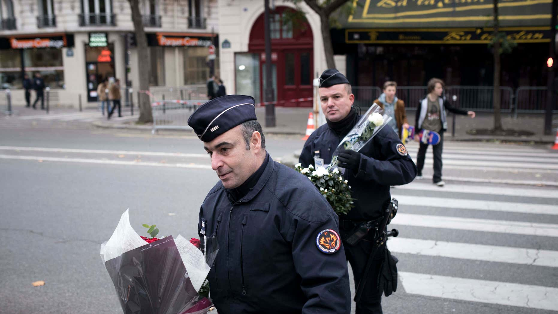 Nov. 12, 2016: Police officers hold flowers, given by people near the Bataclan concert hall in Paris, France.