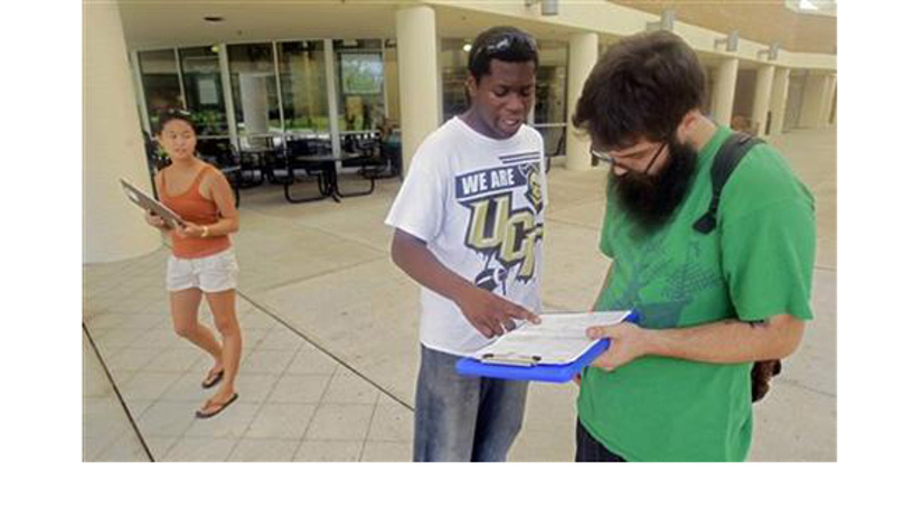 July 31, 2012: Aubrey Marks, left, watches Jordan Allen, center, as he helps student Casey Eirhstaedt, right, register to vote at the University of Central Florida in Orlando, Fla.