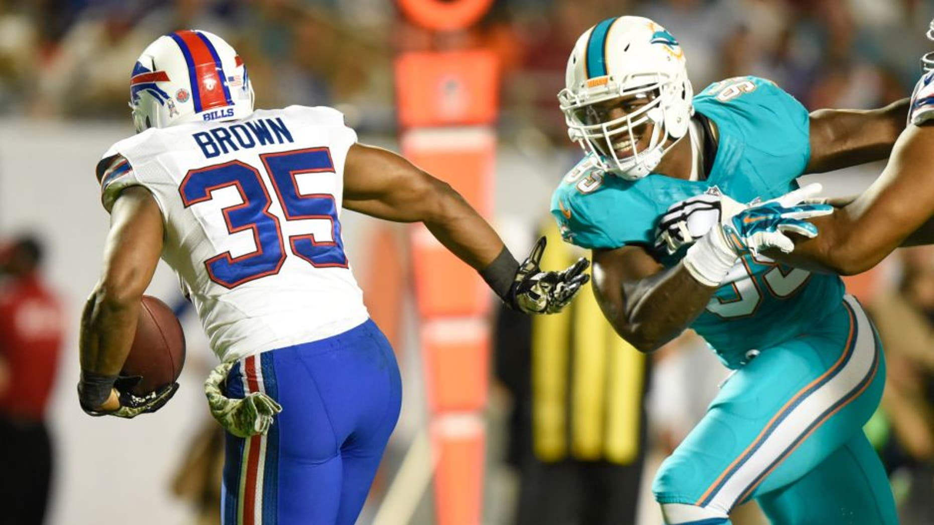 Nov 13, 2014; Miami Gardens, FL, USA; Miami Dolphins long snapper John Denney (92) tries to tackle Buffalo Bills running back Bryce Brown (35) in the first half of the game at Sun Life Stadium. Mandatory Credit: Brad Barr-USA TODAY Sports