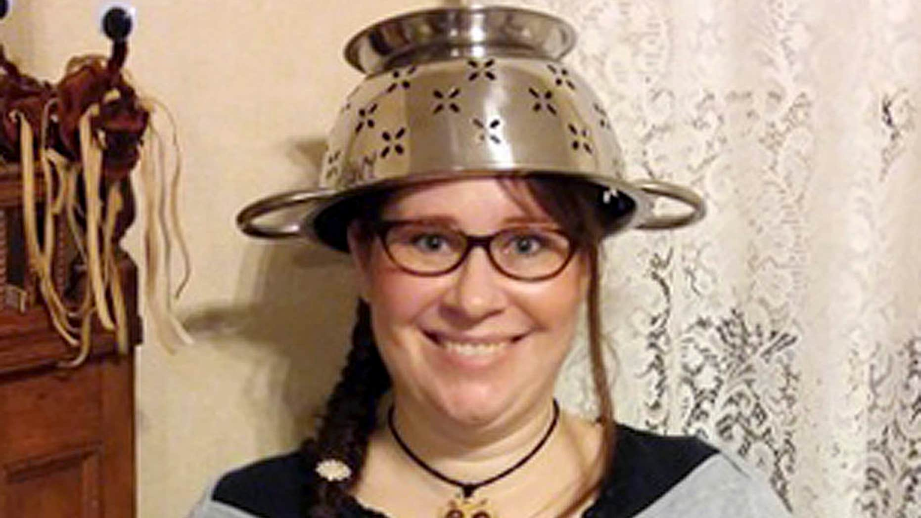 In this Nov. 12, 2015 photo provided by Darrick Fauvel, Lindsay Miller of Lowell, Mass., wears a spaghetti strainer to reflect her religious beliefs while holding her temporary driver license that also bears a photo of her wearing the colander.