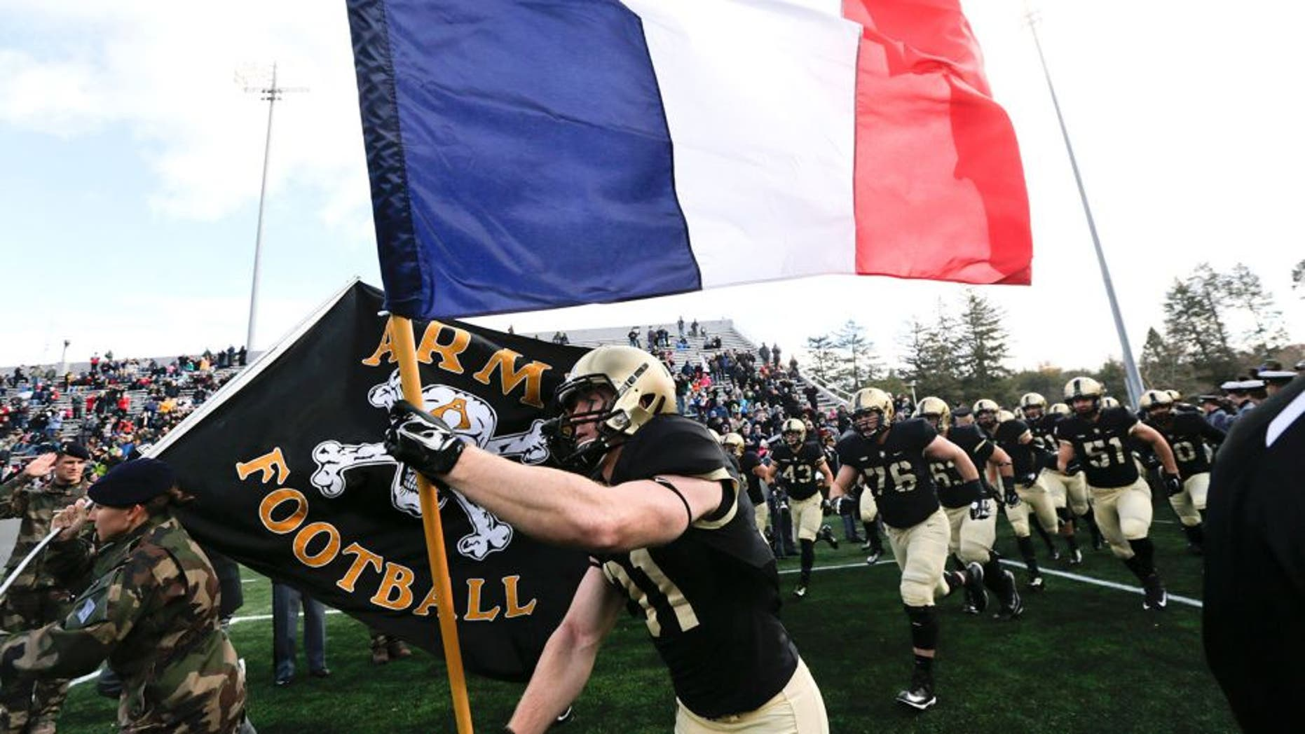 Army defensive back Caleb McNeill carries the flag of France onto the field before an NCAA college football game against Tulane, Saturday, Nov. 14, 2015, in West Point, N.Y. (AP Photo/Mike Groll)