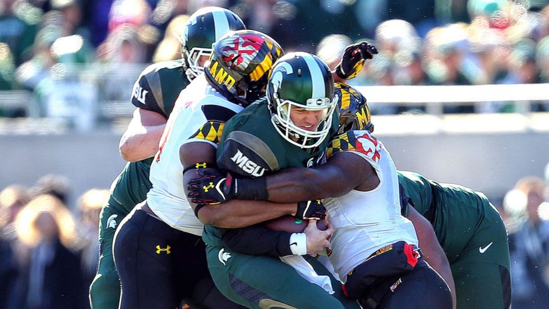 Nov 14, 2015; East Lansing, MI, USA; Michigan State Spartans quarterback Connor Cook (18) carries the ball against the Maryland Terrapins during the first half at Spartan Stadium. Mandatory Credit: Mike Carter-USA TODAY Sports