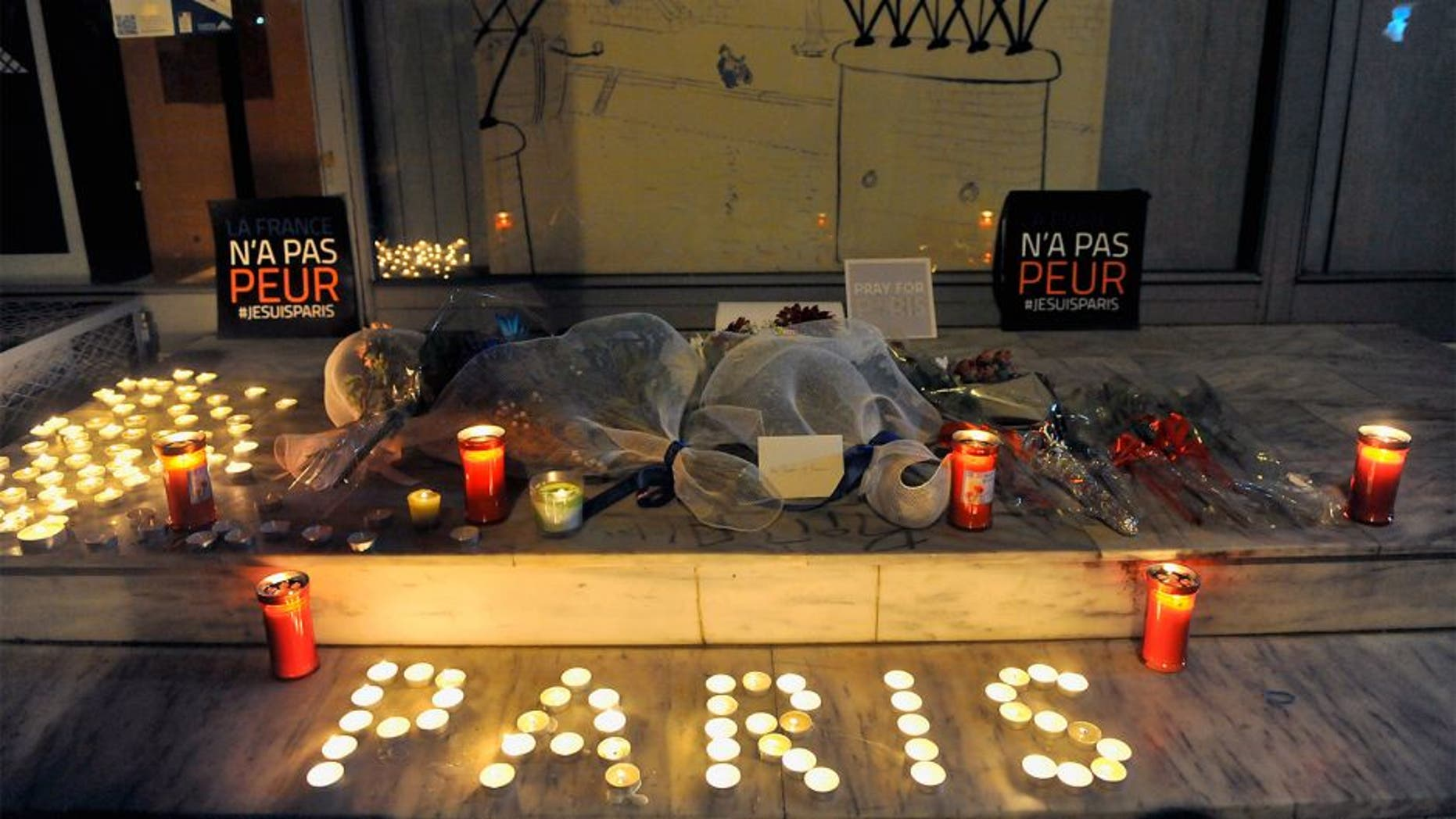 """Flowers and candles reading """"Paris"""" are pictured outside the French consulate in Thessaloniki on November 14, 2015, a day after deadly attacks in Paris. Islamic State jihadists claimed a series of coordinated attacks by gunmen and suicide bombers in Paris that killed at least 128 people in scenes of carnage at a concert hall, restaurants and the national stadium. The placards read """"France is not afraid"""". AFP PHOTO / Sakis Mitrolidis (Photo credit should read SAKIS MITROLIDIS/AFP/Getty Images)"""