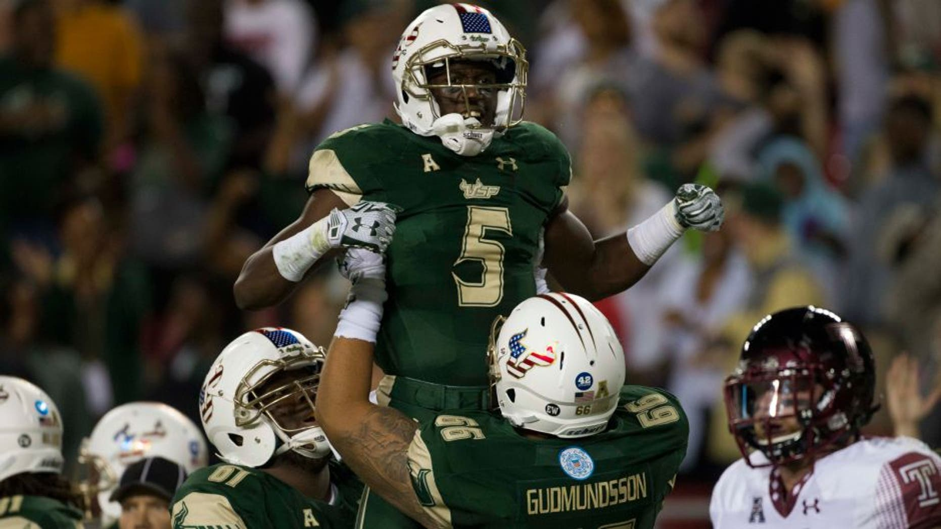Nov 14, 2015; Tampa, FL, USA; South Florida Bulls running back Marlon Mack (5) celebrates with offensive lineman Dominique Threatt (61) and offensive lineman Brynjar Gudmundsson (66) after scoring a touchdown in the second quarter against the Temple Owls at Raymond James Stadium. Mandatory Credit: Logan Bowles-USA TODAY Sports