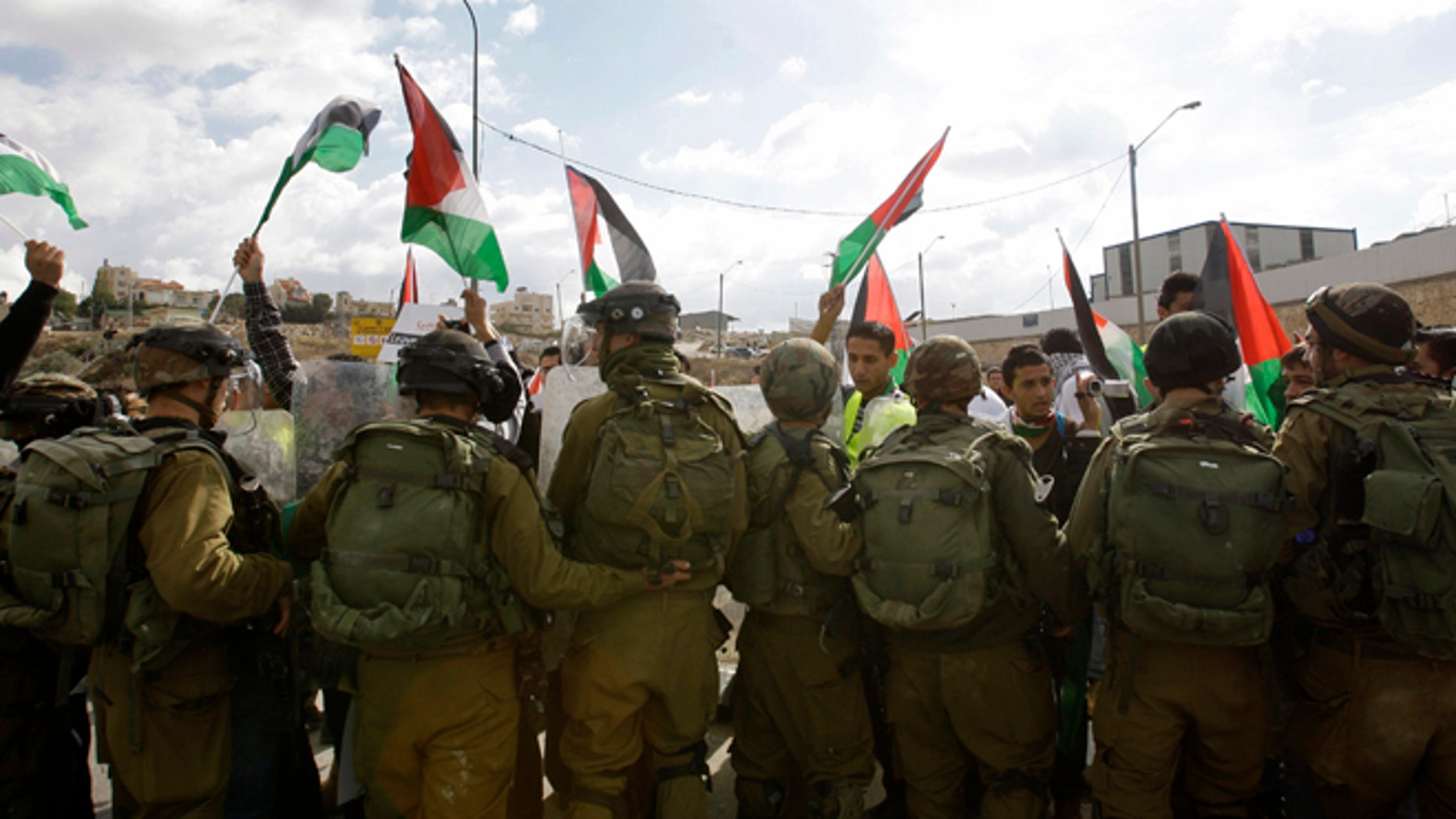 Nov. 14, 2012: Palestinians, foreign and Israeli activists stand in front of Israeli soldiers as they try to block a road near the West Bank town of Bethlehem, as part of a demonstration in support of the Palestinian statehood petition at the U.N. General Assembly.
