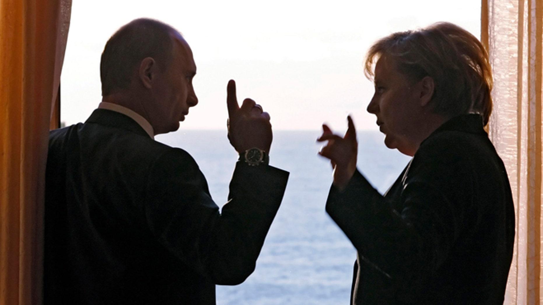 In this Sunday, Jan. 21, 2007 pool file photo German Chancellor Angela Merkel and Russian President Vladimir Putin speak during their meeting in Putin's residence in the Russian Black Sea resort of Sochi.