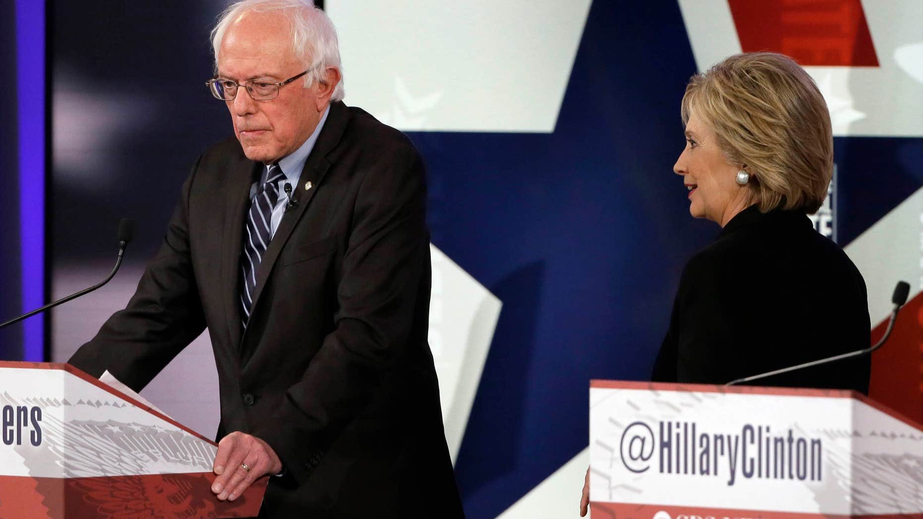 Nov. 14, 2015: Hillary Rodham Clinton, right, walks by Bernie Sanders during a commercial break at a Democratic presidential primary debate in Des Moines, Iowa.