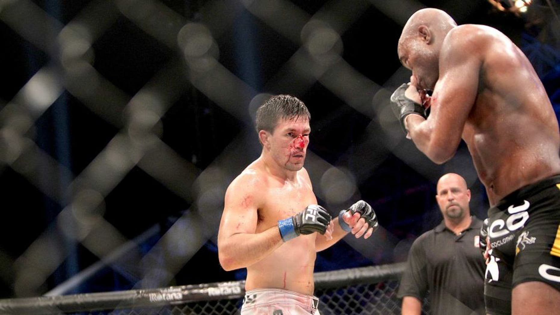 Brazil's Demian Maia (L) bleeds as his compatriot Anderson Silva prepares for an attack during their Ultimate Fighting Championship (UFC) 112 middleweight bout in Abu Dhabi on April 10, 2010. Silva won the fight. AFP PHOTO/KARIM SAHIB (Photo credit should read KARIM SAHIB/AFP/Getty Images)