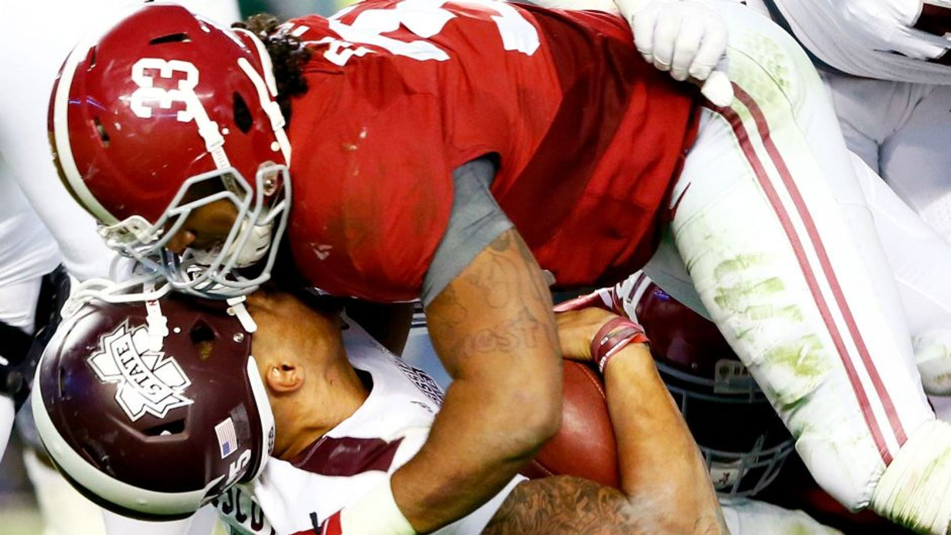 Dak Prescott #15 of the Mississippi State Bulldogs loses his helmet as he is tackled by Trey DePriest #33 of the Alabama Crimson Tide at Bryant-Denny Stadium on November 15, 2014 in Tuscaloosa, Alabama. (Photo by Kevin C. Cox/Getty Images)