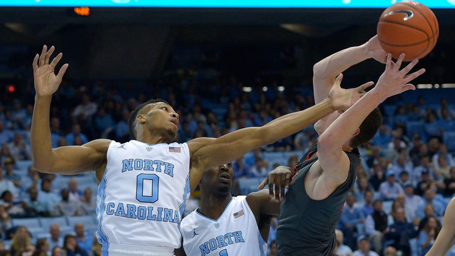 CHAPEL HILL, NC - NOVEMBER 15: Nate Britt #0 and Theo Pinson #1 of the North Carolina Tar Heels battle Matija Milin #34 of the Fairfield Stags during the first half of their game at the Dean Smith Center on November 15, 2015 in Chapel Hill, North Carolina. (Photo by Grant Halverson/Getty Images)