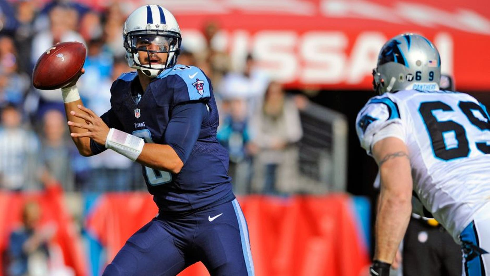 Nov 15, 2015; Nashville, TN, USA; Tennessee Titans quarterback Marcus Mariota (8) rolls out of the pocket chased by Carolina Panthers defensive end Jared Allen (69) during the first half at Nissan Stadium. Mandatory Credit: Christopher Hanewinckel-USA TODAY Sports
