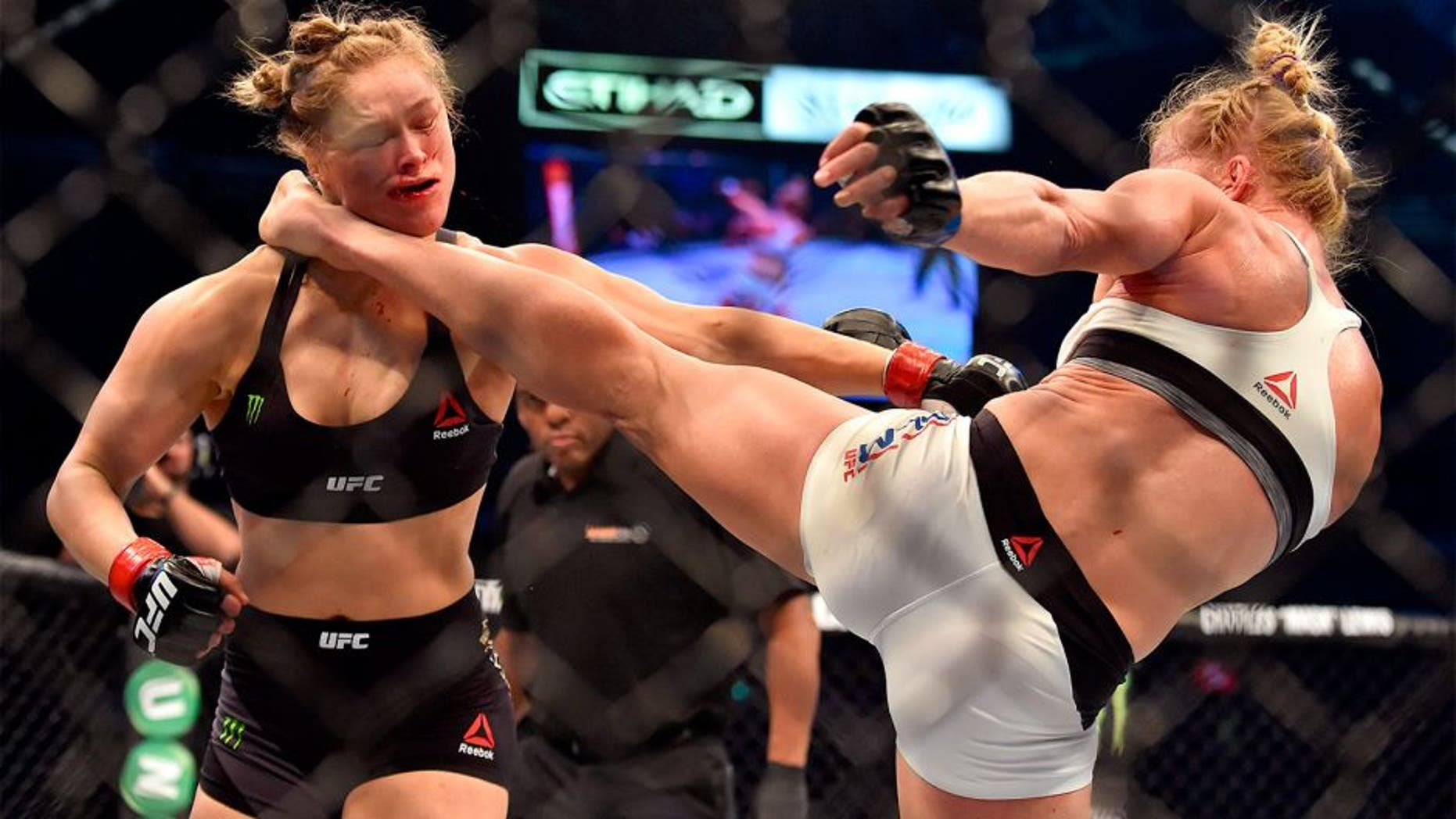 Holly Holm of the US (R) lands a kick to the neck to knock out compatriot Ronda Rousey and win the UFC title fight in Melbourne on November 15, 2015. RESTRICTED TO EDITORIAL USE NO ADVERTISING USE NO PROMOTIONAL USE NO MERCHANDISING USE. AFP PHOTO/Paul CROCK (Photo credit should read PAUL CROCK/AFP/Getty Images)