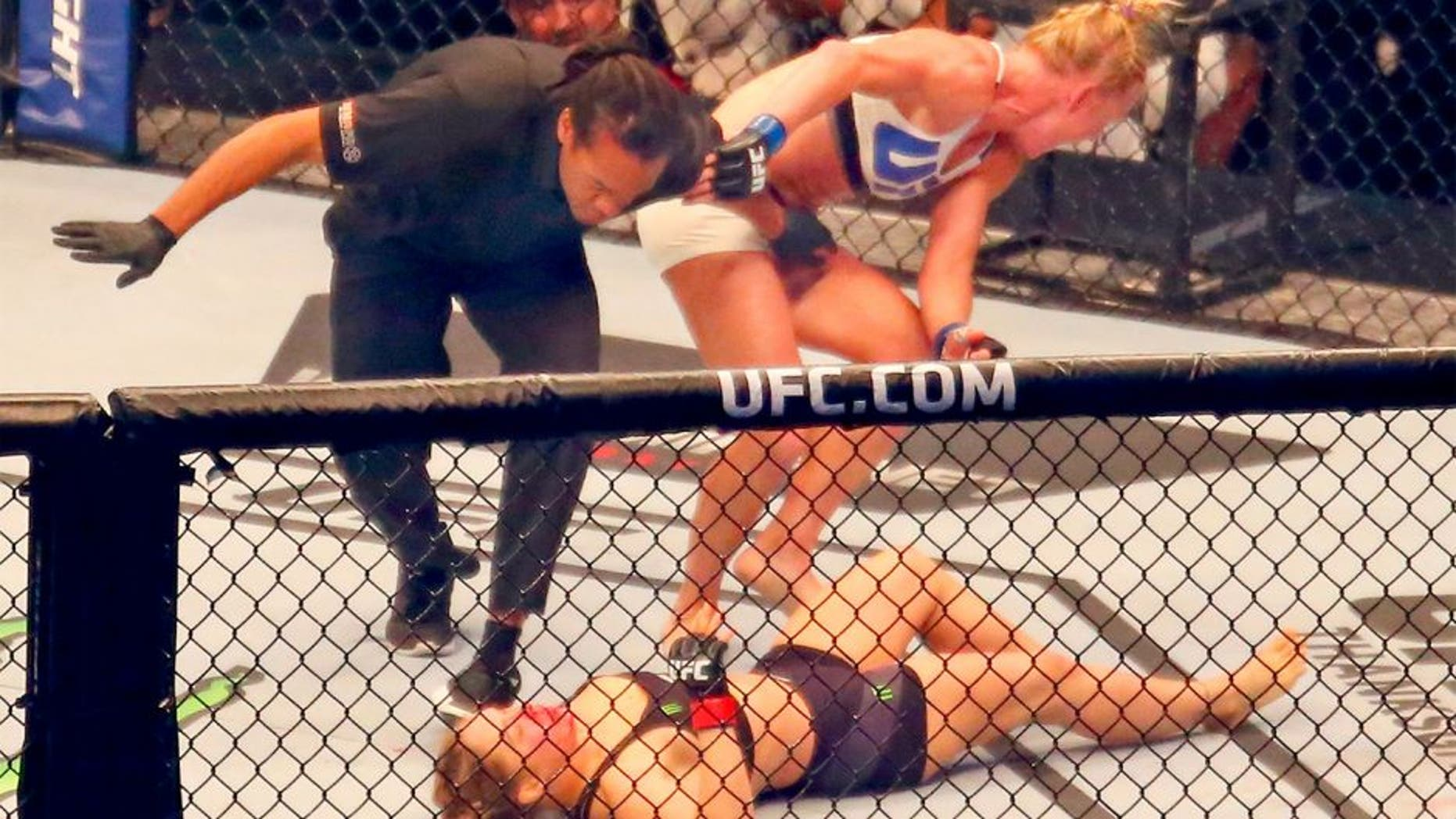 MELBOURNE, AUSTRALIA - NOVEMBER 15: Referee Herb Dean ends the fight as New UFC women's bantamweight champion Holly Holm of the United States starts to celebrate her victory over Ronda Rousey of the United States in their UFC women's bantamweight championship bout during the UFC 193 event at Etihad Stadium on November 15, 2015 in Melbourne, Australia. (Photo by Scott Barbour /Zuffa LLC/Zuffa LLC via Getty Images)
