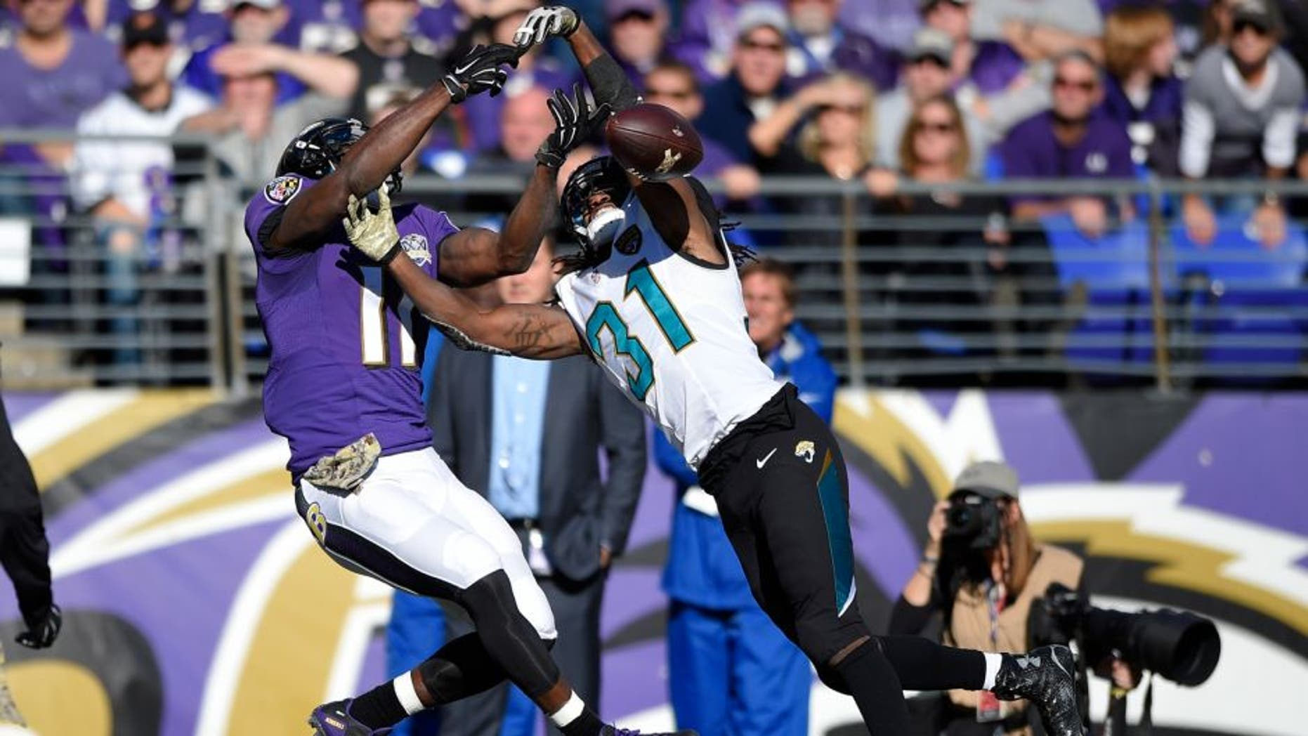 Jacksonville Jaguars cornerback Davon House, right, breaks up a pass-attempt to Baltimore Ravens wide receiver Kamar Aiken in the first half an NFL football game, Sunday, Nov. 15, 2015, in Baltimore. (AP Photo/Nick Wass)