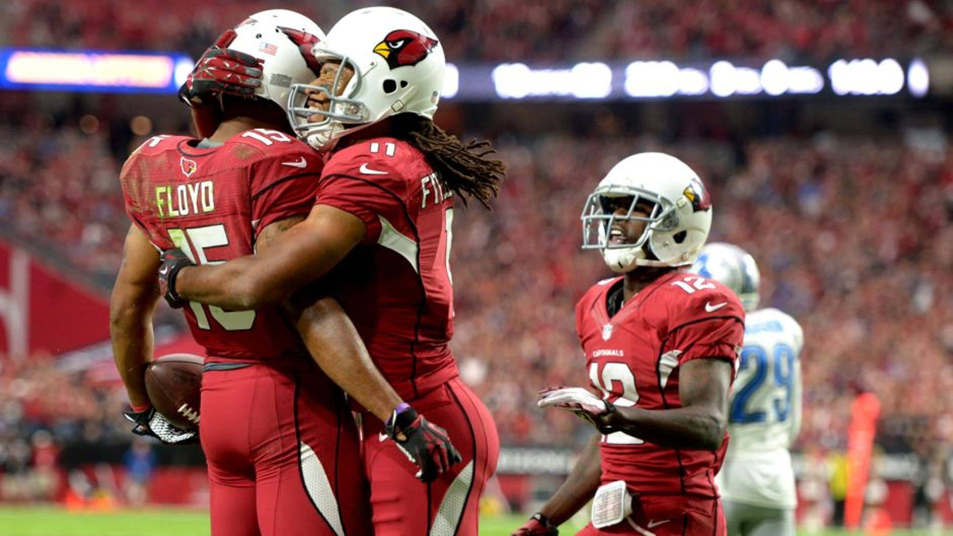 Nov 16, 2014; Glendale, AZ, USA; Arizona Cardinals receiver Michael Floyd (15) celebrates with receivers Larry Fitzgerald (11) and John Brown (12) after scoring on a 12-yard touchdown pass in the first quarter against the Detroit Lions at University of Phoenix Stadium. Mandatory Credit: Kirby Lee-USA TODAY Sports