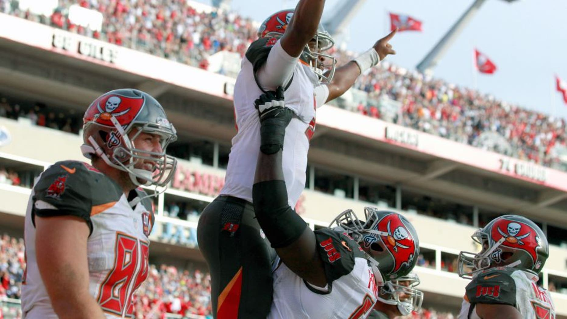 Nov 15, 2015; Tampa, FL, USA; Tampa Bay Buccaneers quarterback Jameis Winston (3) is congratulated by tTampa Bay Buccaneers offensive guard Kevin Pamphile (64) as he ran the ball in for a touchdown during the fourth quarter against the Dallas Cowboys at Raymond James Stadium. Mandatory Credit: Kim Klement-USA TODAY Sports