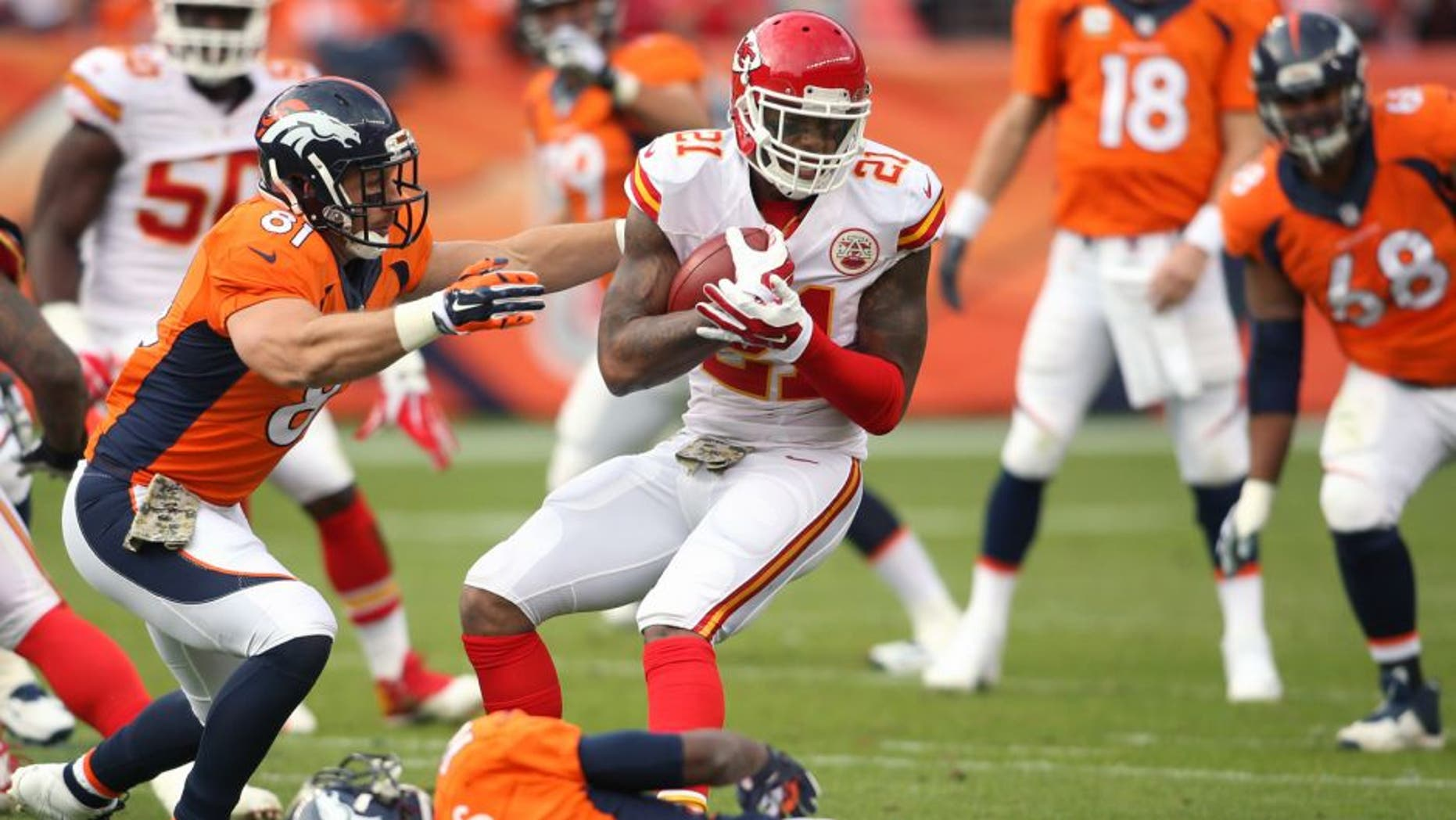 Nov 15, 2015; Denver, CO, USA; Kansas City Chiefs cornerback Sean Smith (21) attempts to avoid being tackled by Denver Broncos tight end Owen Daniels (81) and wide receiver Emmanuel Sanders (10) after intercepting a pass throw by Denver Broncos quarterback Peyton Manning (18) during the first half at Sports Authority Field at Mile High. Mandatory Credit: Chris Humphreys-USA TODAY Sports