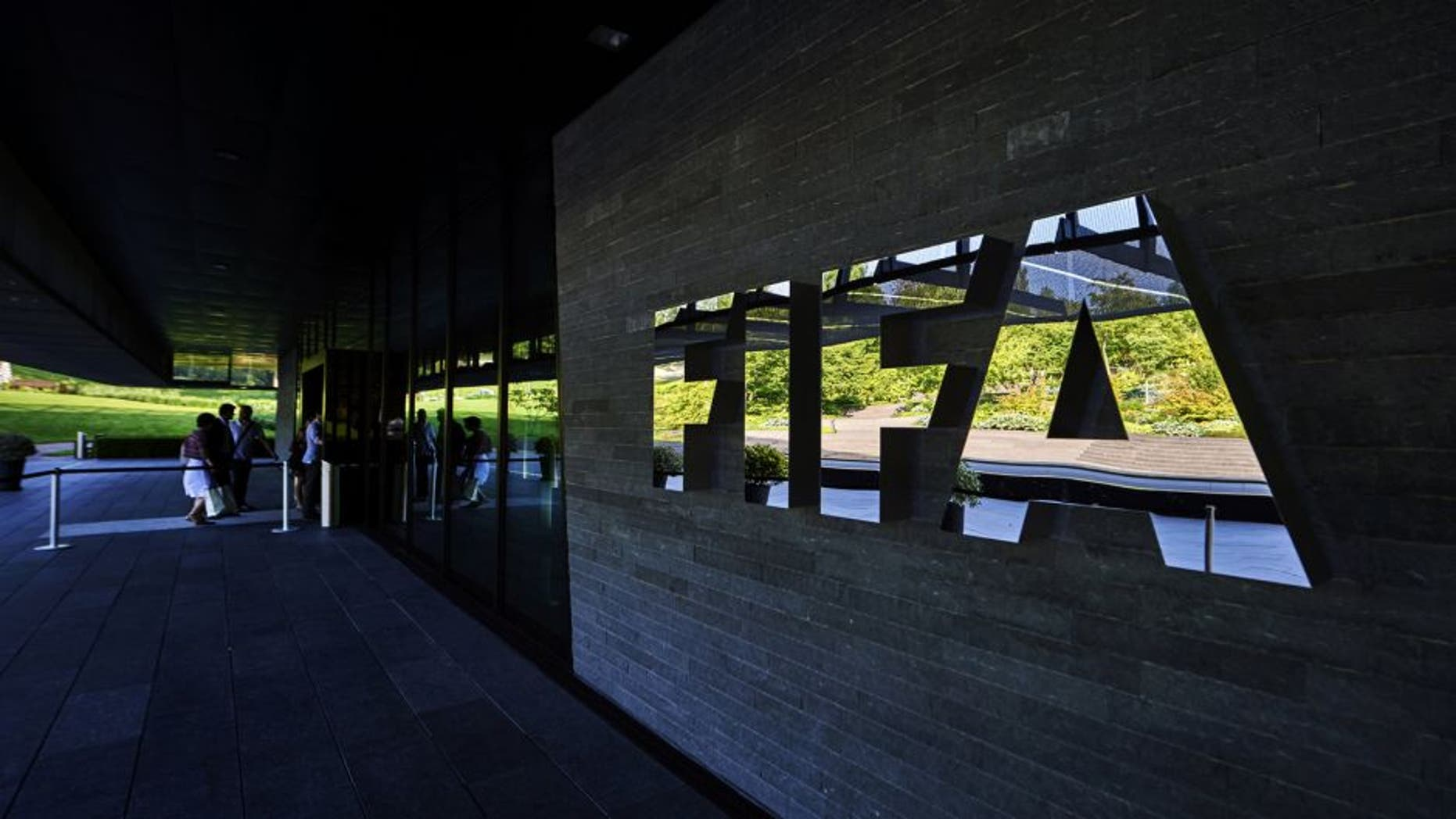 FIFA employees enter at the FIFA headquarters on June 3, 2015 in Zurich. Blatter resigned on June 2, 2015 as president of FIFA as a mounting corruption scandal engulfed world football's governing body. The 79-year-old Swiss official, FIFA president for 17 years and only reelected on May 29, said a special congress would be called as soon as possible to elect a successor. AFP PHOTO / MICHAEL BUHOLZER (Photo credit should read MICHAEL BUHOLZER/AFP/Getty Images)
