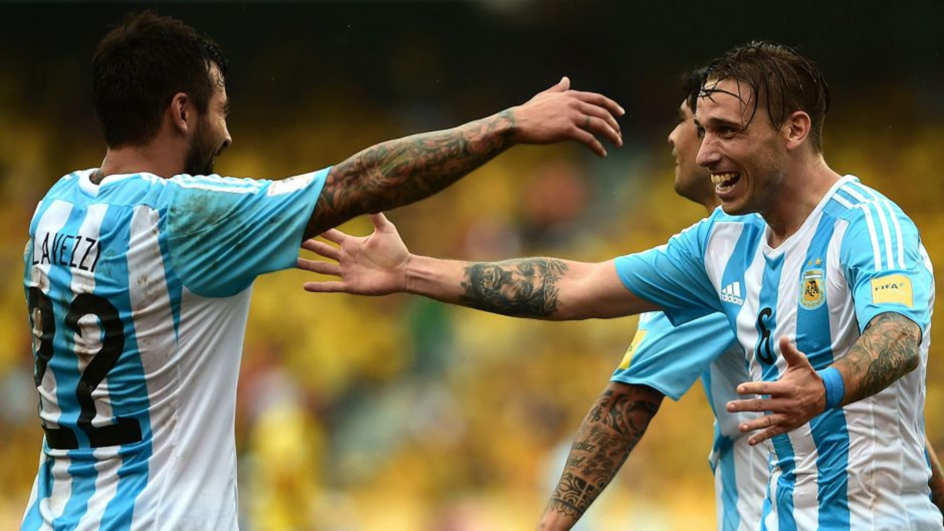 Argentina's Lucas Biglia (R) celebrates with Ezequiel Lavezzi after scoring against Colombia during their Russia 2018 FIFA World Cup South American Qualifiers football match, in Barranquilla on November 17, 2015. AFP PHOTO / LUIS ROBAYO (Photo credit should read LUIS ROBAYO/AFP/Getty Images)