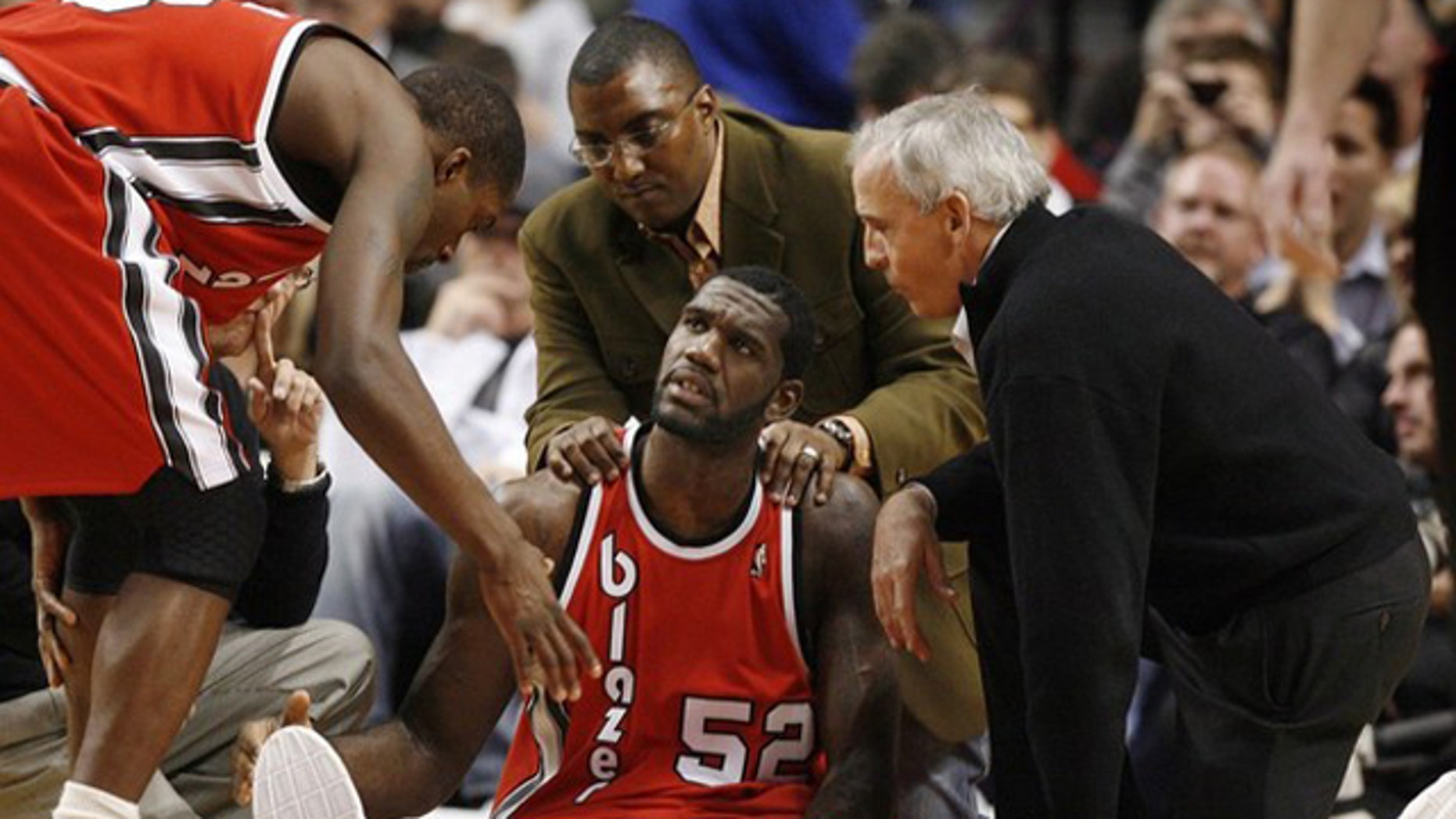 Portland Trail Blazers center Greg Oden (52) receives encouragement from teammate Martell Webster (L) as medical personel attend to his broken left leg during the first quarter of their NBA basketball game in Portland, Oregon on December 5, 2009.