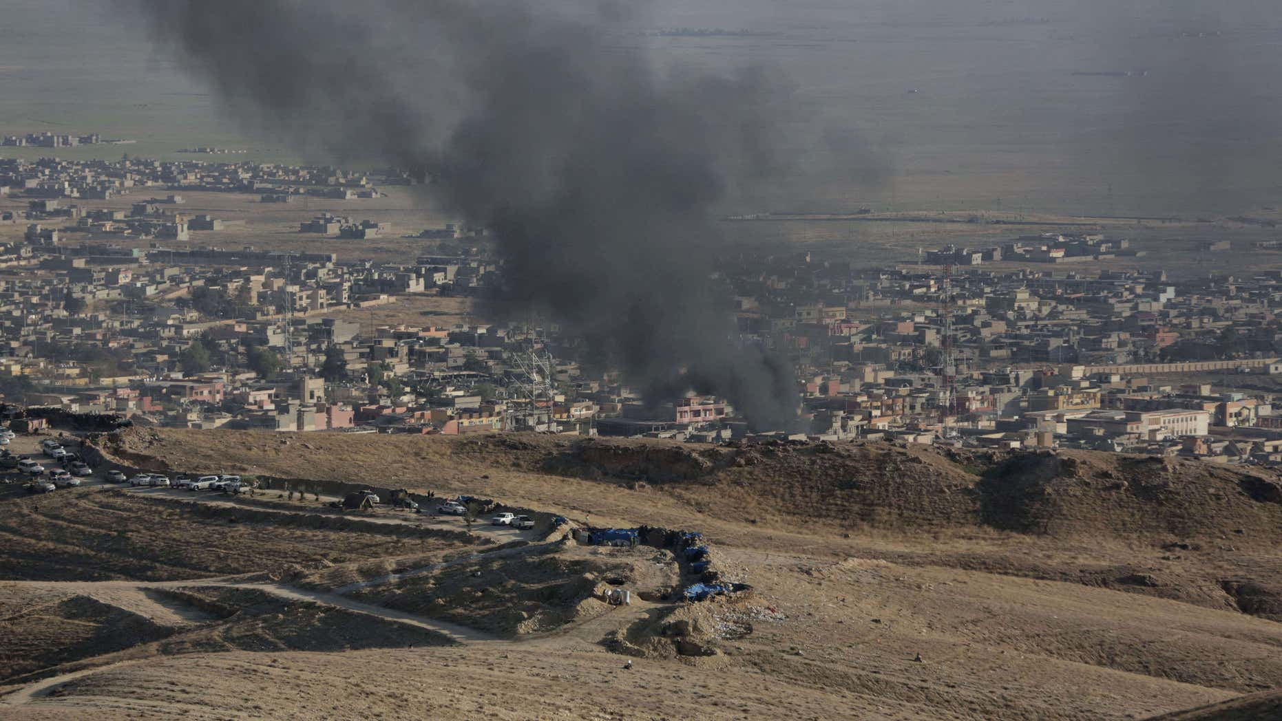 Nov. 12, 2015: Smoke rises over Sinjar, northern Iraq from oil fires set by Islamic State militants as Kurdish Iraqi fighters, backed by U.S.-led airstrikes, launch a major assault.