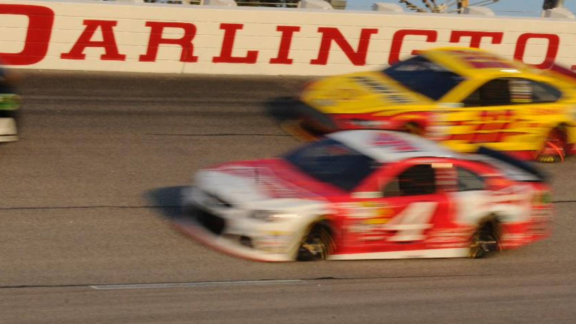 FILE - In this April 12, 2014, file photo, Kevin Harvick (4) and Joey Logano (22) race during a NASCAR Sprint Cup series auto race at Darlington Raceway in Darlington, S.C. The superspeedway that had been a springtime staple of NASCAR the past 10 seasons has gone more than a year since engines were revved for the Southern 500.  (AP Photo/Mike McCarn, FIle)