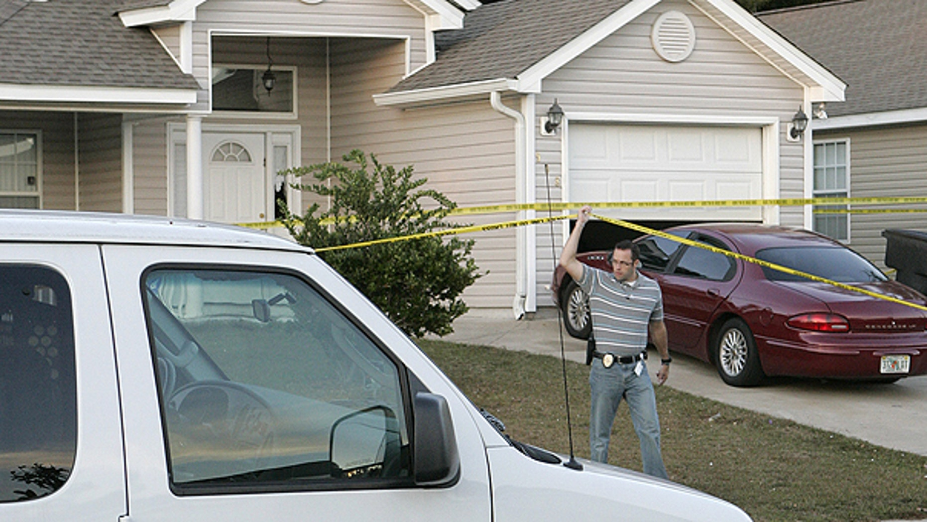 Nov. 20: An investigator lifts police tape to pass under at a home where a woman and three children were slain in Tallahassee, Fla.
