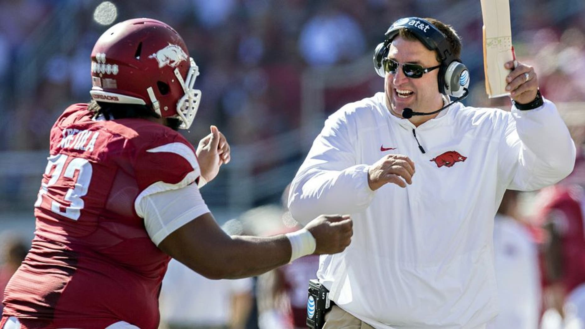 FAYETTEVILLE, AR - OCTOBER 25: Head Coach Bret Bielema and Sebastian Tretola #73 of the Arkansas Razorbacks celebrate after Tretola throws a touchdown pass against the UAB Blazers at Razorback Stadium on October 25, 2014 in Fayetteville, Arkansas. The Razorbacks defeated the Blazers 45-17. (Photo by Wesley Hitt/Getty Images)