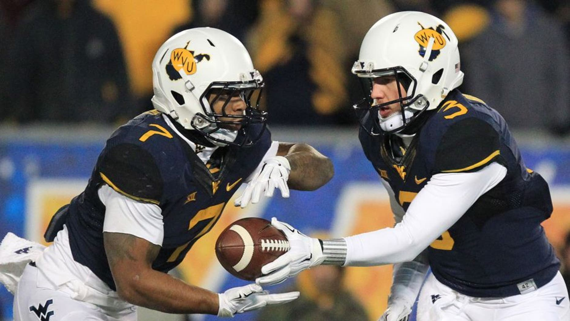 West Virginia quarterback Skyler Howard (3) hands the ball off to Rushel Shell (7) during the second half of an NCAA college football game against Kansas State in Morgantown, W.Va., on Thursday, Nov. 20, 2014. Kansas State won 26-20. (AP Photo/Chris Jackson)
