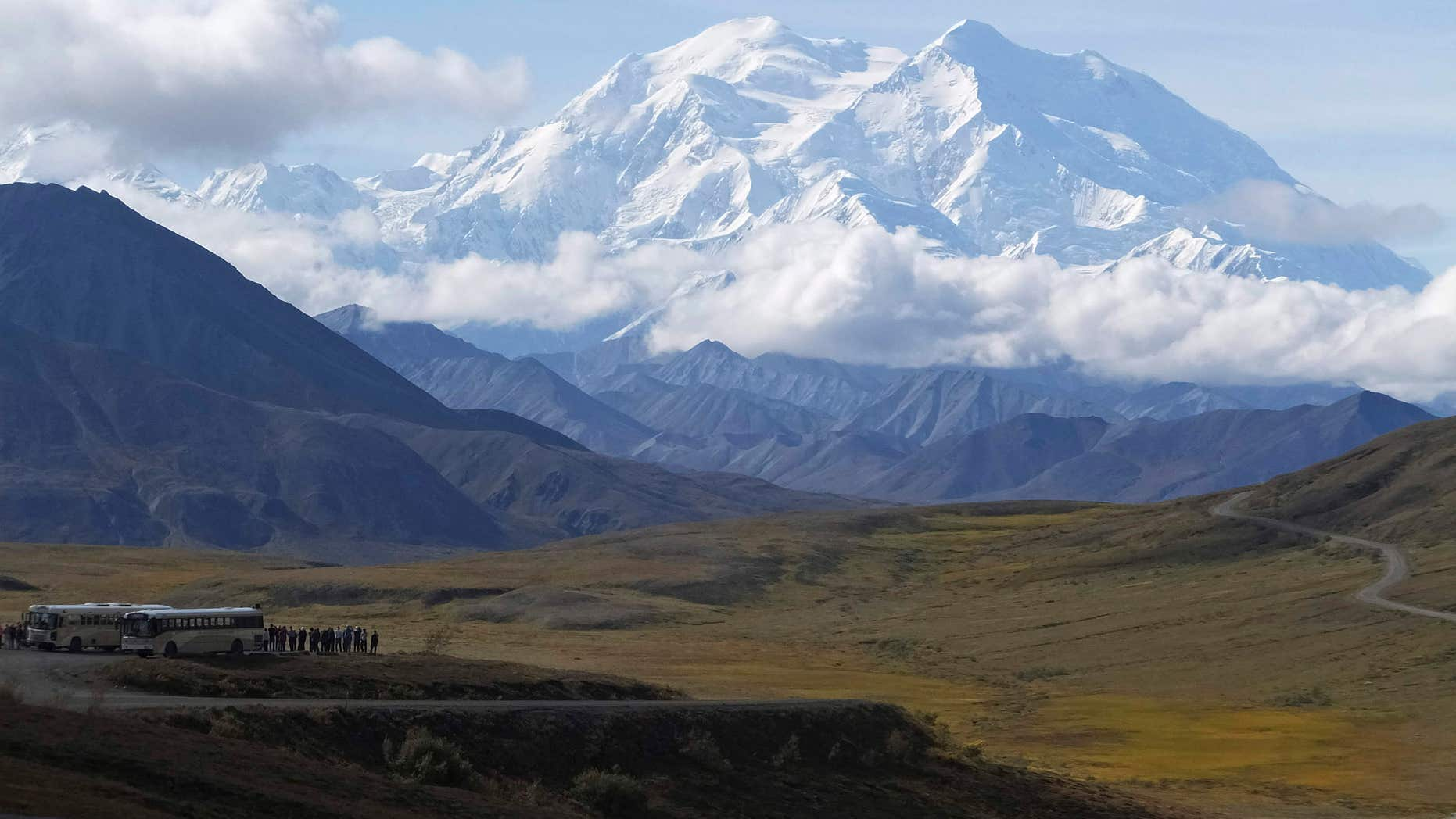 In this photo taken Aug. 26, 2016, sightseeing buses and tourists are seen at a pullout popular for taking in views of North America's tallest peak, Denali, in Denali National Park and Preserve, Alaska.