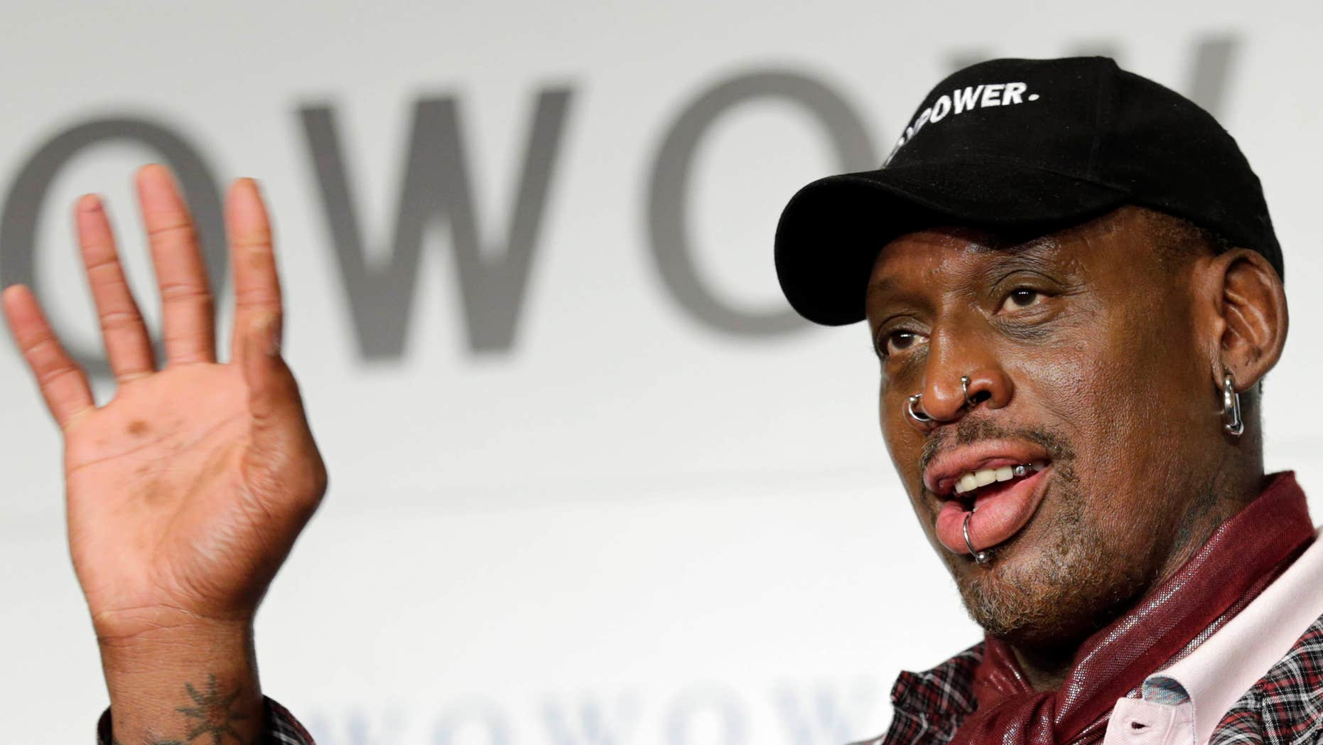 FILE - In this Oct. 25, 2013, file photo, former basketball player Dennis Rodman waves during a news conference in Tokyo.