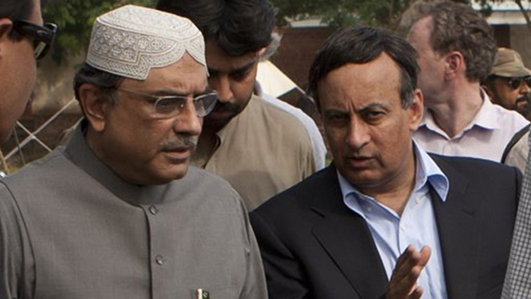 August 19, 2010: Pakistan's Ambassador in Washington Hussain Haqqani, right, talks with Pakistan's President Asif Ali Zardari in Multan, Pakistan.