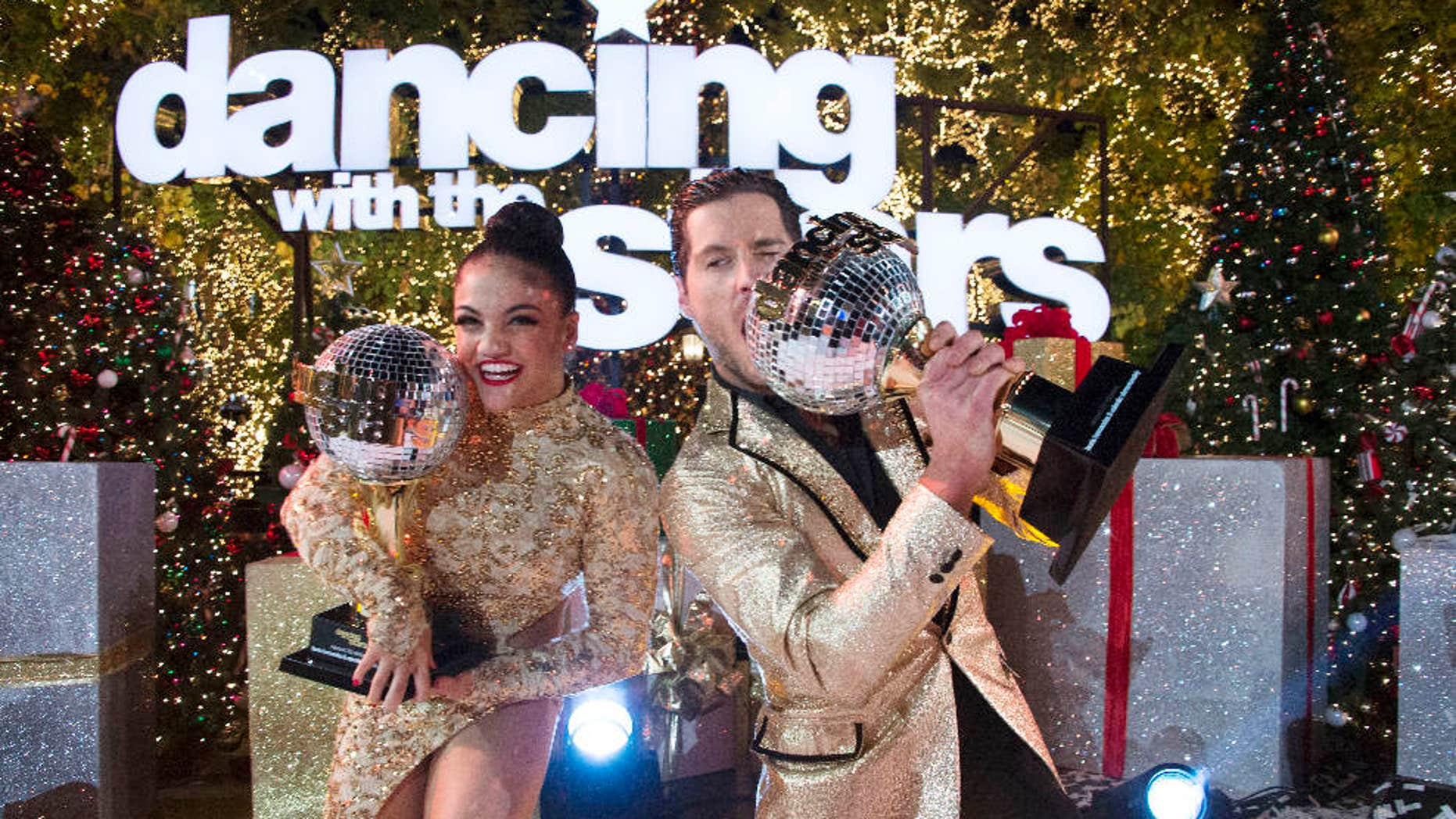 """In this Nov. 22, 2016 photo released by ABC, Laurie Hernandez, left, and Val Chmerkovskiy celebrate after winning the 23rd season of the celebrity dance competition series, """"Dancing With The Stars,"""" in Los Angeles."""